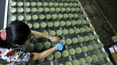 ADVANCE FOR MONDAY, DEC. 3. - In this Aug. 30, 2012 photo, production line worker Xiao Yins-Wong straightens the wick in the candles at Chesapeake Bay Candle factory in Glen Burnie Md. Chesapeake Bay Candle's first factory was established in China in 1995. Last summer, it opened a new factory to handle increased demand from China. This time, the factory was built in Glen Burnie, outside Baltimore. (AP Photo/Jose Luis Magana