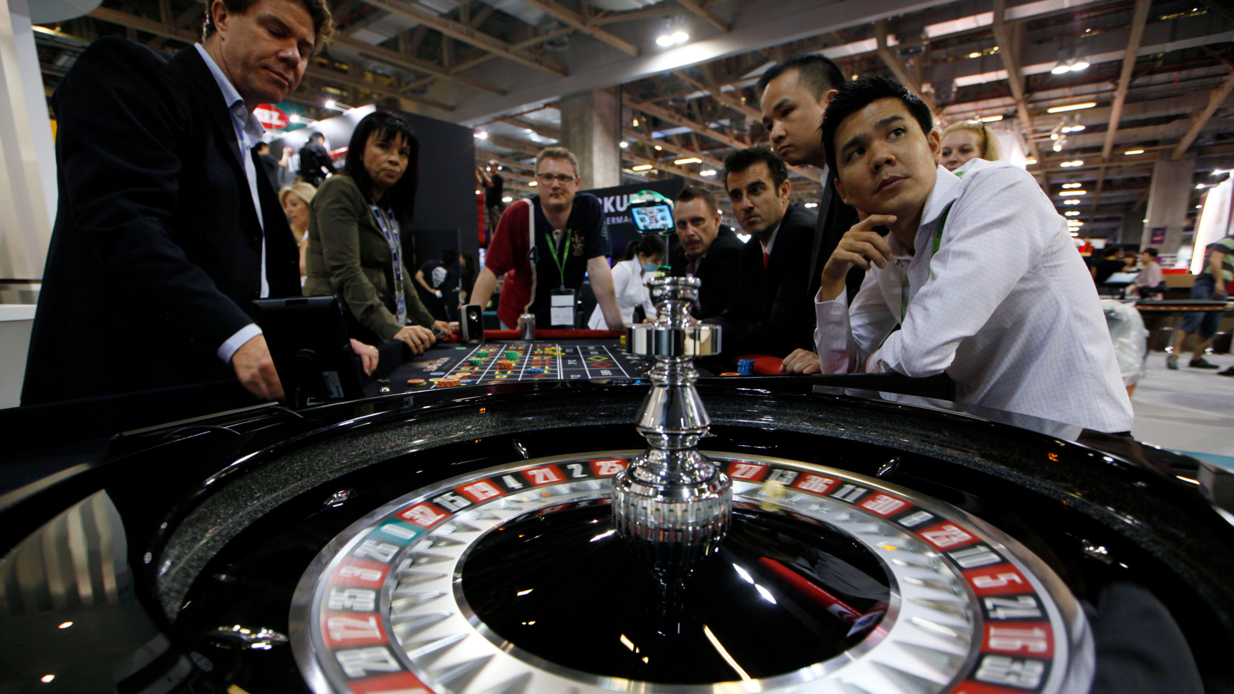 Exhibitor staff members sit in front of the roulette at a gambling table at Gaming Expo Asia in Macau Tuesday, May 22, 2012. The Global Gaming Expo Asia held between May 22-24 is a trade show and conference for the Asian gaming market.  (AP Photo/Kin Cheung)