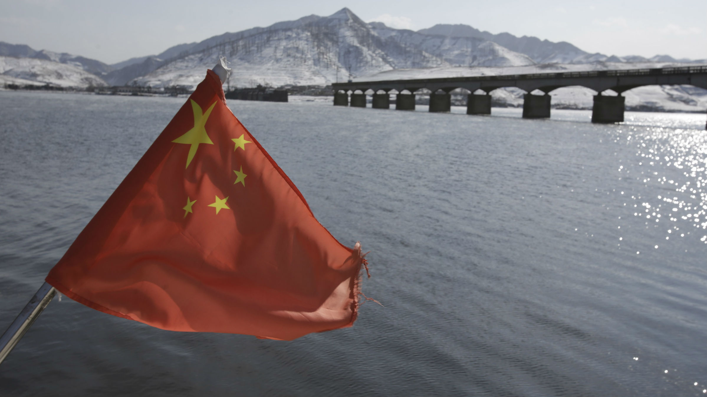 A Chinese flag is hoisted near the Hekou Bridge, right, linking China and North Korea, which was bombed in the 1950's during the Korean War, in Hekou, China on Thursday, Feb. 7, 2013. North Korea vowed last month to carry out its third nuclear test but has said nothing about timing. As a result, the building suspense in Seoul has prompted many to look at the dates Pyongyang has chosen for past atomic tests, as well as rocket and missile launches.