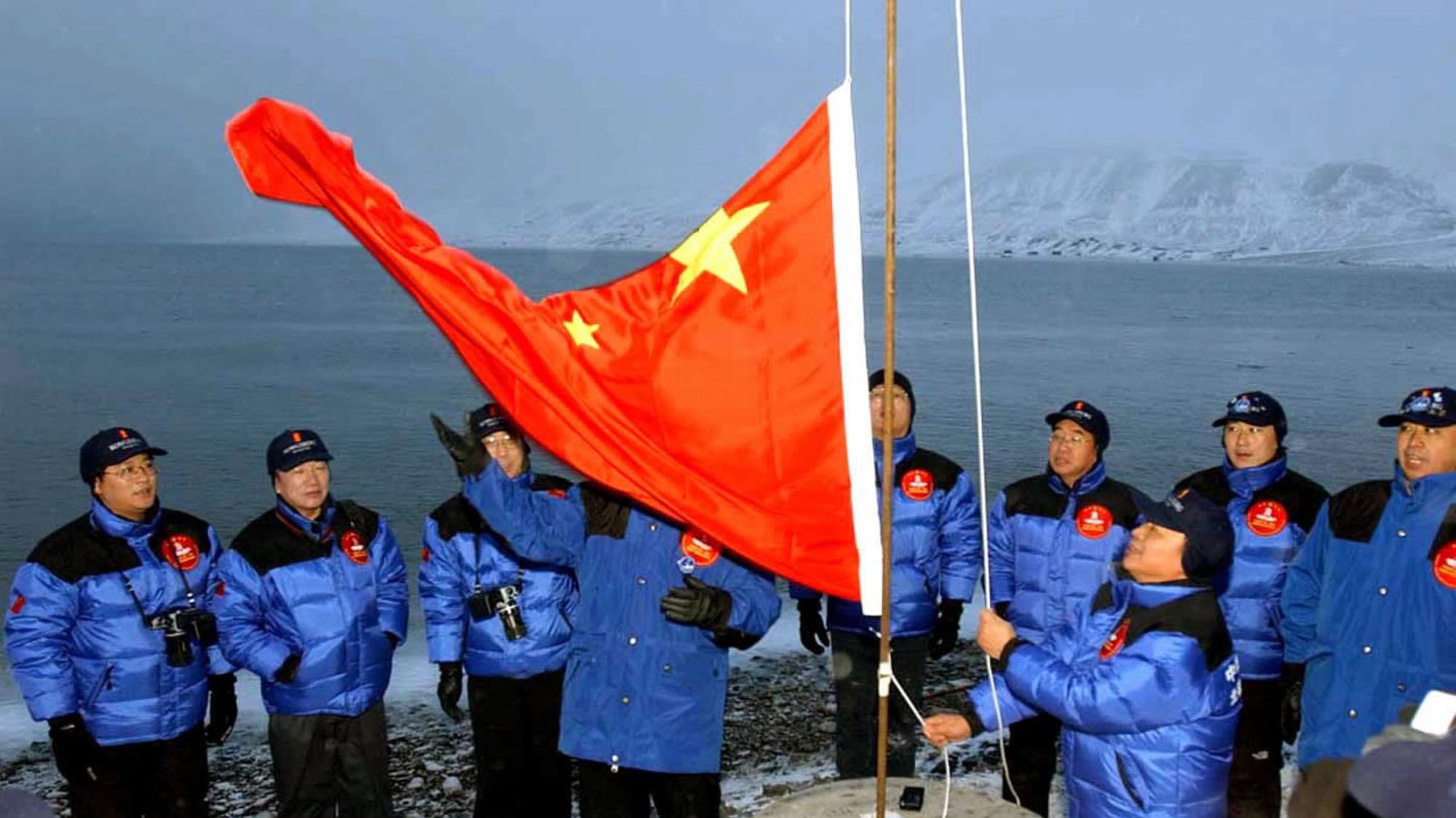 Members of the Chinese Yilite-Mulin Arctic Pole Expedition raise the Chinese national flag in Longyearbyen on Svalbard, Norway, to set the site of a Chinese research station on Wednesday, Oct. 31, 2001. (AP Photo/Xinhua/Yuan Man