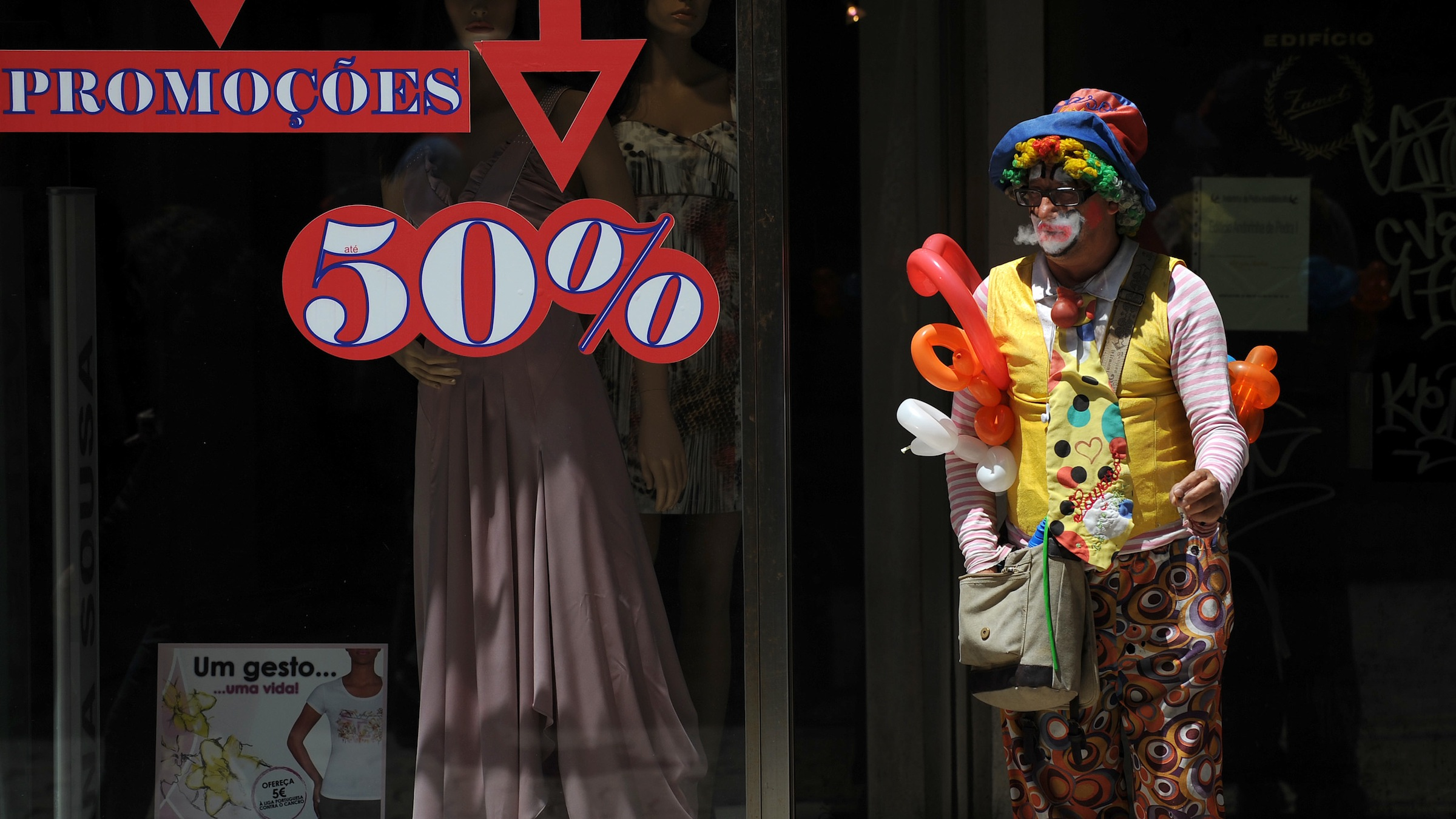 A street clown makes a pause for a cigarette, Thursday, July 7 2011, in downtown Porto, Portugal. Portugal's financial plight has deepened. Borrowing rates jumped higher and stocks slumped after its bonds were downgraded to junk status. Portugal's hopes of slowly emerging from its debt crisis were knocked by ratings agency Moody's, which downgraded Portugal's debt four notches and said the country will likely follow Greece in needing a second rescue package.(AP Photo/Paulo Duarte)