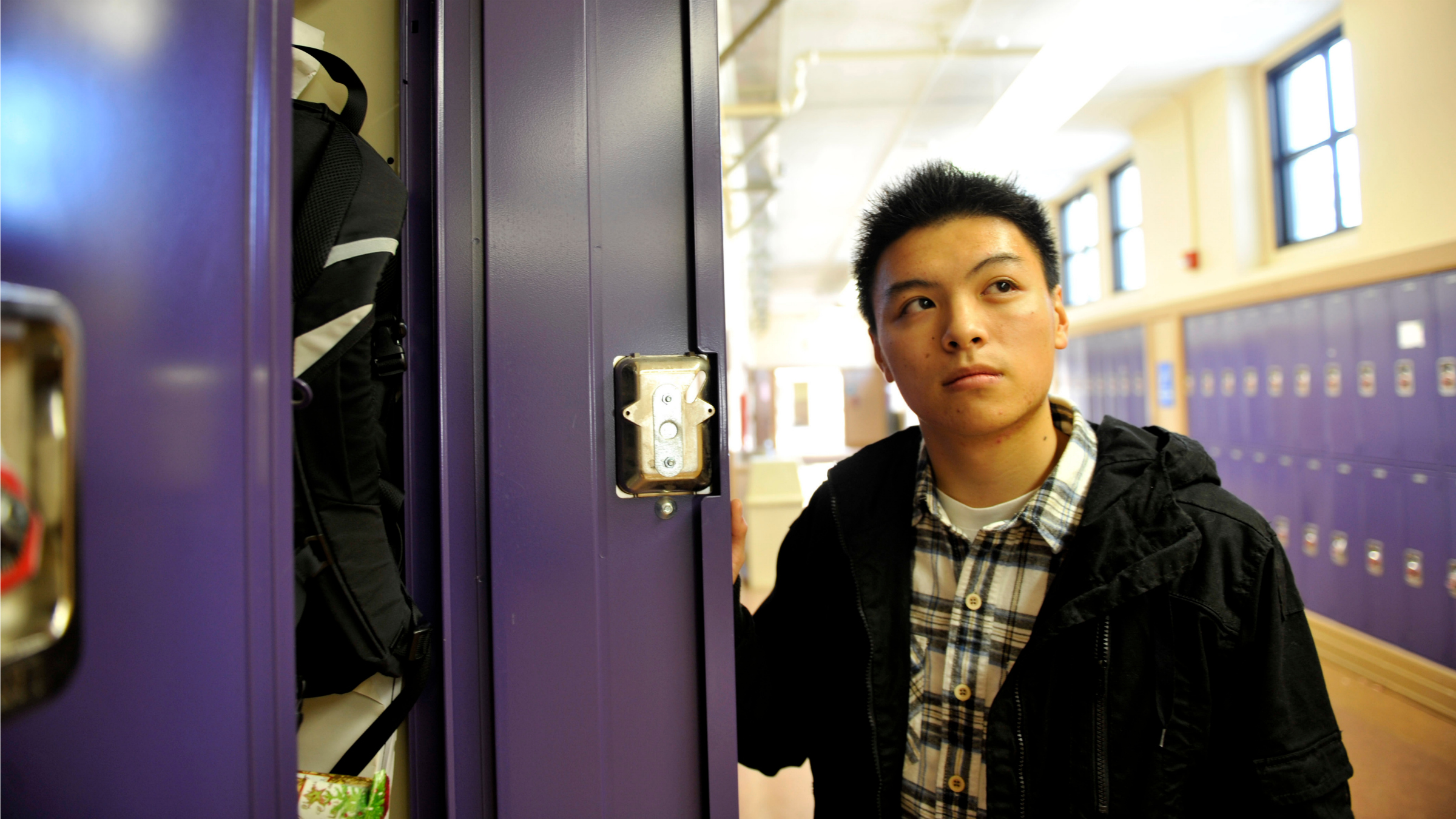 High School student daydreams by his locker.