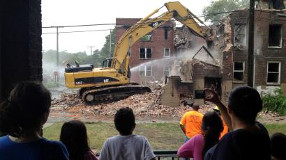 Demolition crews start tearing down four vacant apartment buildings in southwest Detroit, Thursday, July 19, 2012. The buildings, earlier gutted by fire, are among nearly 160 in the area targeted for demolition and were identified with help from community residents.