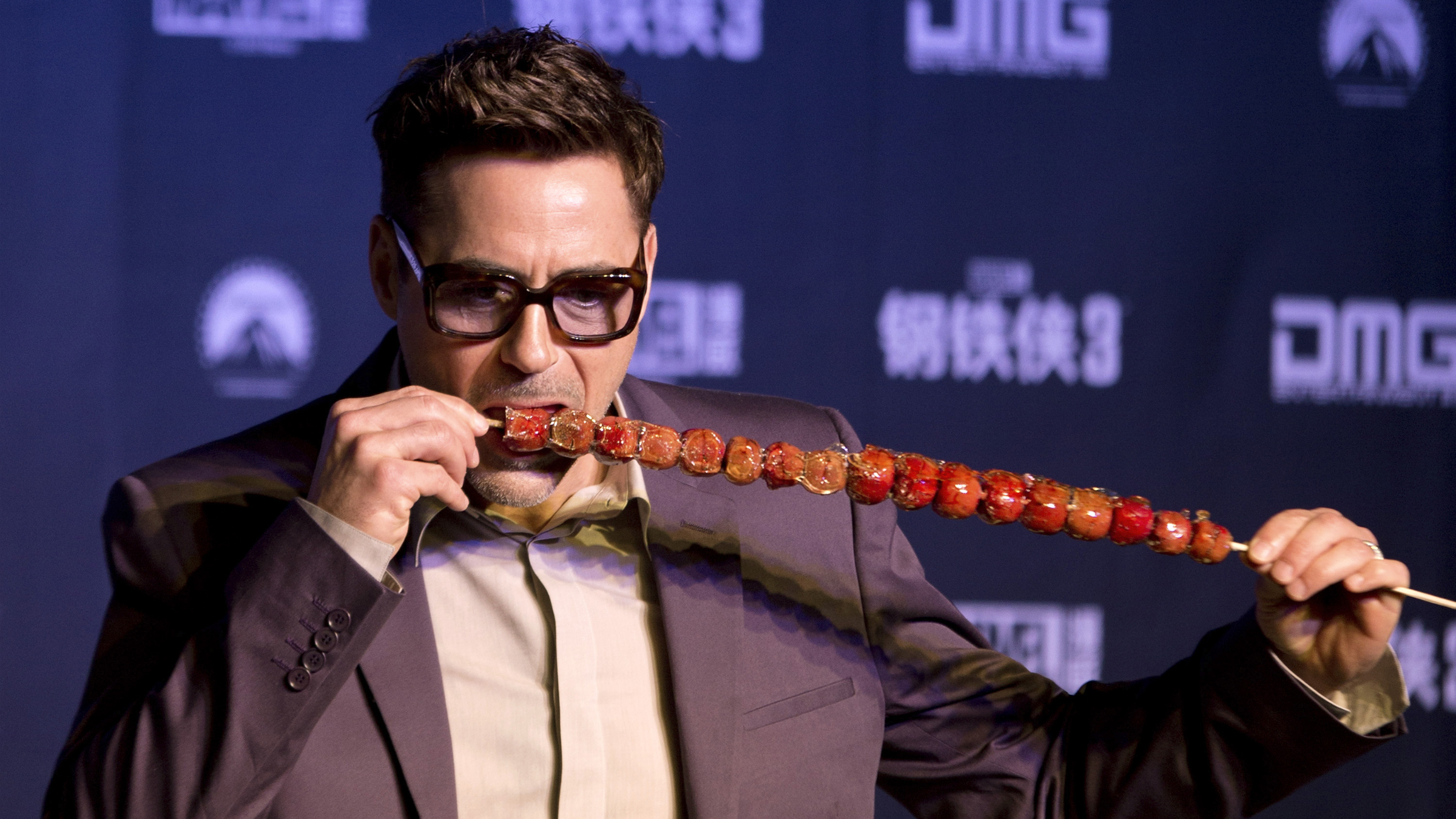 """U.S. actor Robert Downey Jr. tries out """"bingtanghulu,"""" a traditional Chinese snack, during a world premiere event of his new movie """"Iron Man 3"""" at a Beijing hotel Saturday, April 6, 2013. (AP Photo/Andy Wong"""