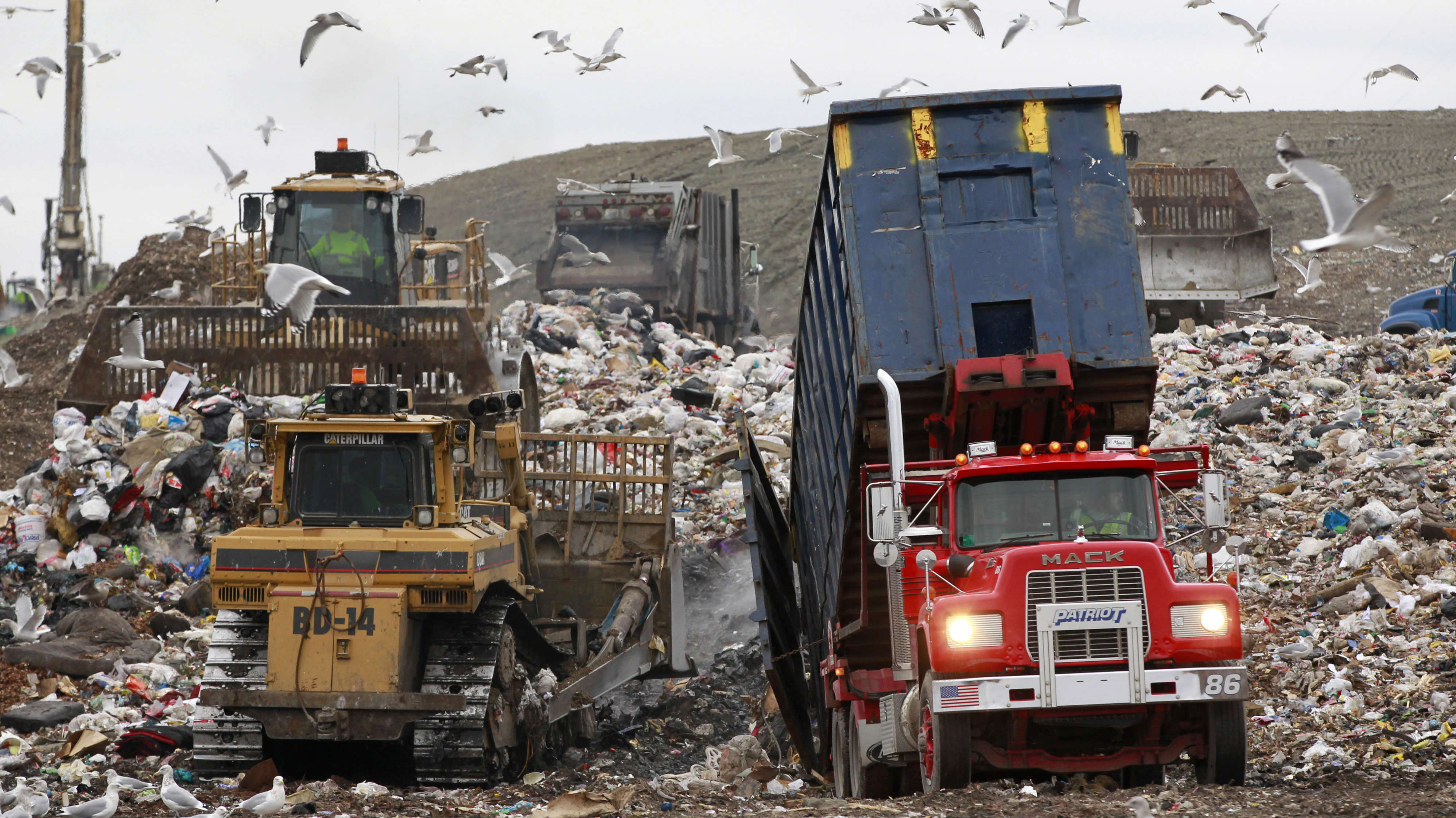 Garbage trucks, right and behind, empty their load as bulldozers process the waste at the Central Landfill, in Johnston, R.I., Wednesday, Dec. 14, 2011. Johnston Mayor Joseph Polisena sued the state's main landfill Wednesday over noxious odors that have plagued residents for several weeks. (AP Photo/Steven Senne)