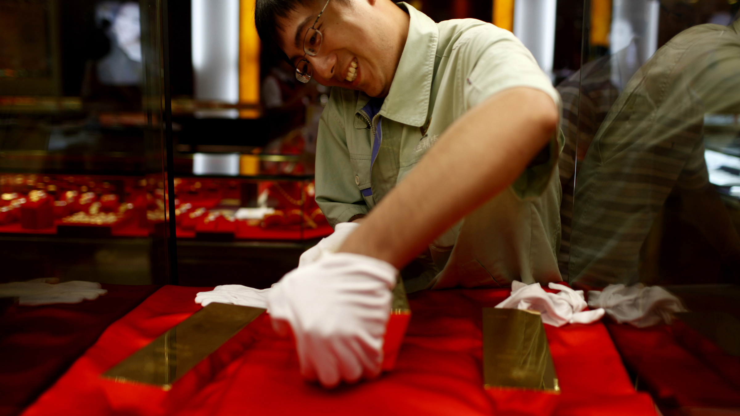 A salesman tries to carry a 25 kilograms gold brick to show at a gold products store on September 1, 2012 in Zhaoyuan, China. Zhaoyuan, the Chinese gold capital known as China's gold production base, produces 1/8 of the nation's mined gold and has gold reserves that account for 1/7 of the nation's total. It has created a gold industry which involves exploration, mining, smelting and refining gold and silver products. China has been the world's largest gold producer for five years , (Photo by Hong Wu/Getty Images