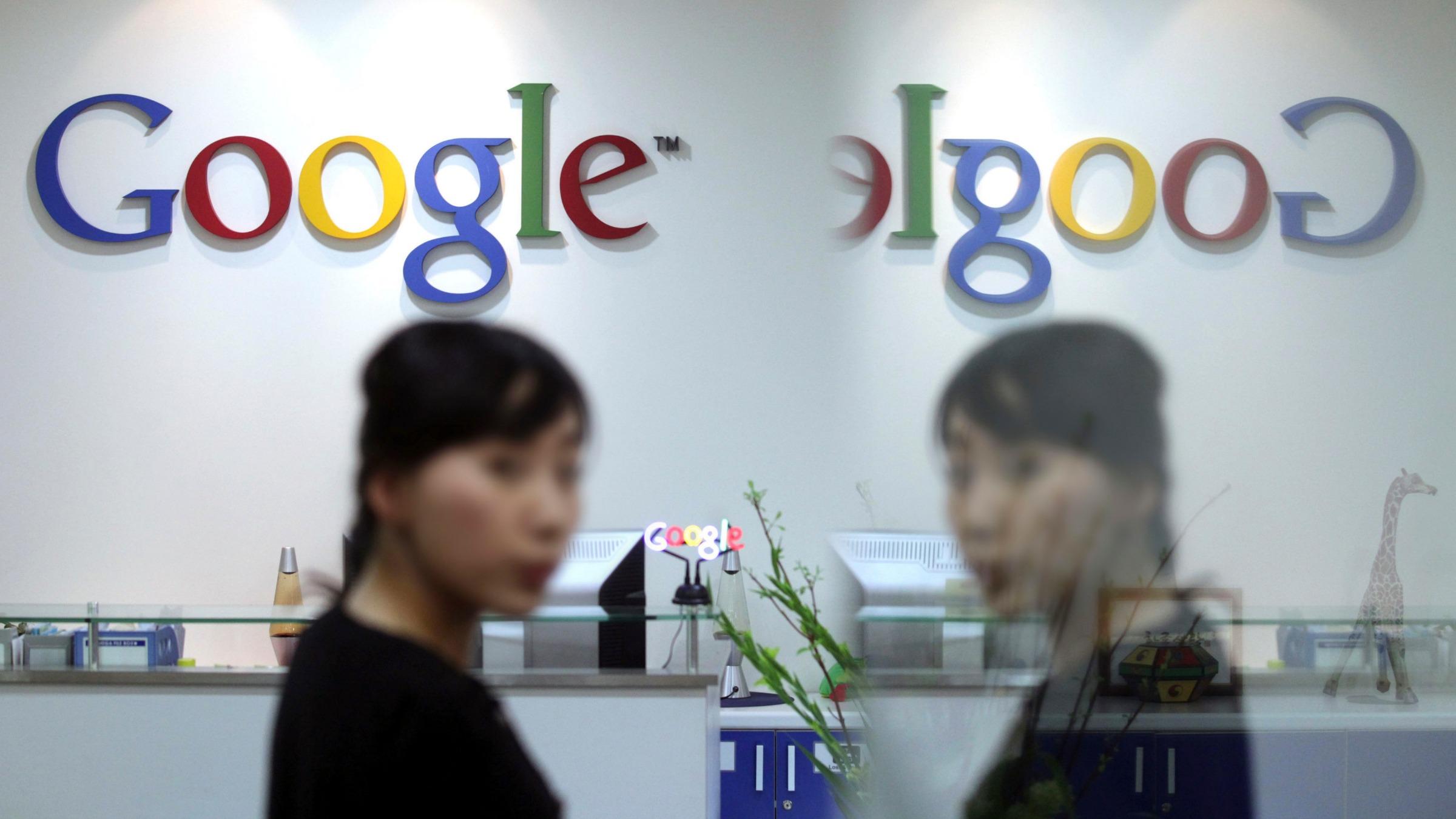 An employee of Google Korea is reflected on the glass door.