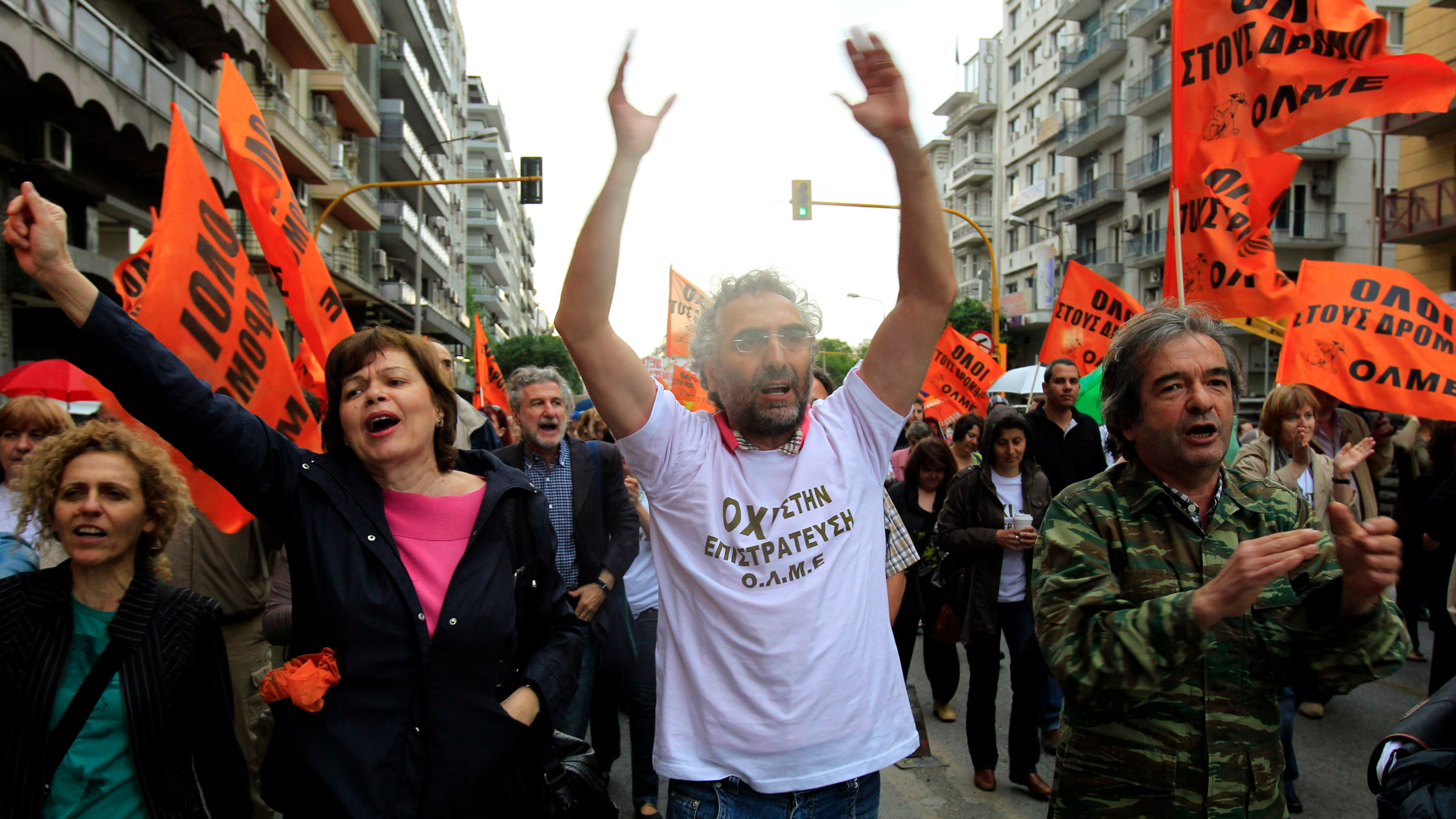 """Teachers wearing t-shirts that read """"No to the Civil Mobilization"""" shout slogans during a protest in central Thessaloniki on Monday, May 13, 2013. Greece's conservative-led government has issued a civil mobilization order forcing state school teachers to work during university entrance exams later in May."""