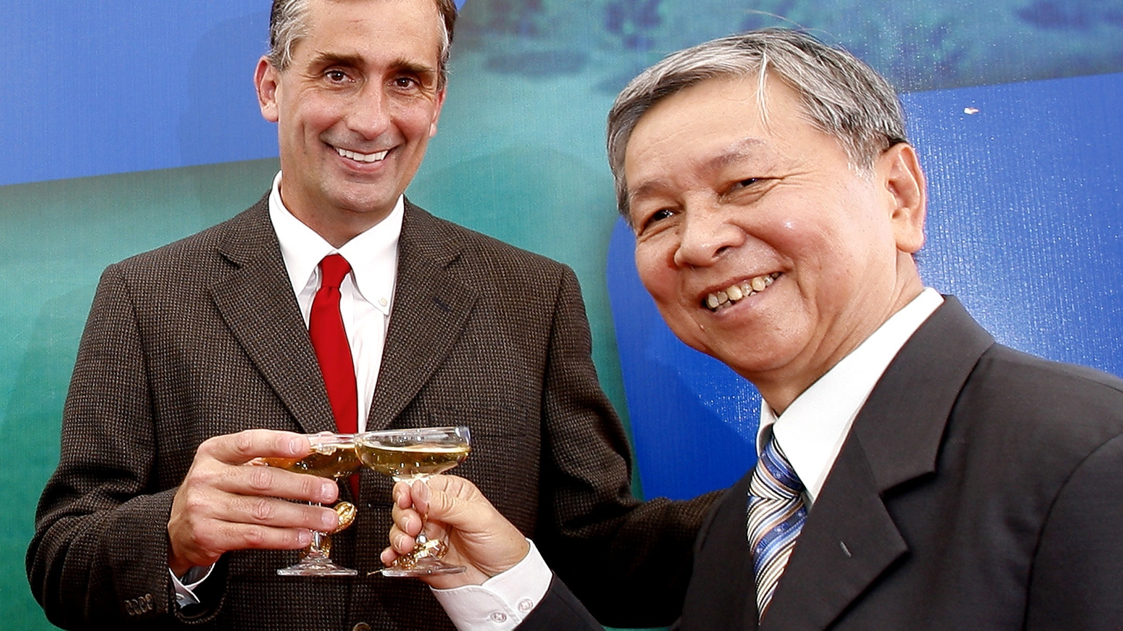 Intel Corp. Vice President and General Manager of Assembly and Test Brian Krzanich, left, and  former Chairmain of Saigon High Tech Park Pham Chanh Truc clink their glasses at the start of Construction Ceremony of the Assembly and Test Facility of Intel's chipset products at Saigon High Tech Park in Ho Chi Minh city, South Vietnam, on Wednesday, March 28, 2007. This construction with the 500,000 square foot (46,451 square meter) facility in South Vietnam, was first announced of Intel's US$1 bilion investment in November 2006. It will take about 18 months with production expected in 2009 and could eventually employ as many as 4,000 people once completed. (AP Photo/Le Quang Nhat)