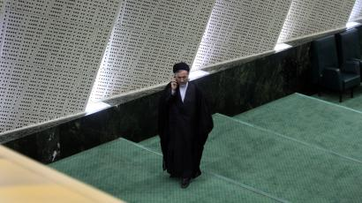 An unidentified Iranian clerical lawmaker talks on his cell phone as he walks through the parliament, in Tehran, Iran, Wednesday, Aug. 17, 2011. Iran's internal power struggles are shifting into election mode with hard-line political forces banding together to groom candidates for next year's parliamentary elections and punish allies of President Mahmoud Ahmadinejad.
