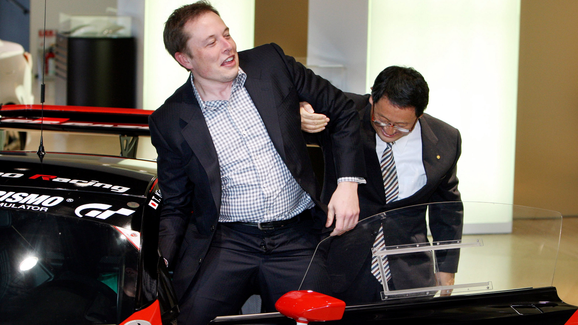 Toyota CEO Akio Toyoda,right, helps Tesla CEO Elon Musk for leaves from Lexus racing car at Toyota  showroom  in Tokyo, Friday, Nov 12, 2010.