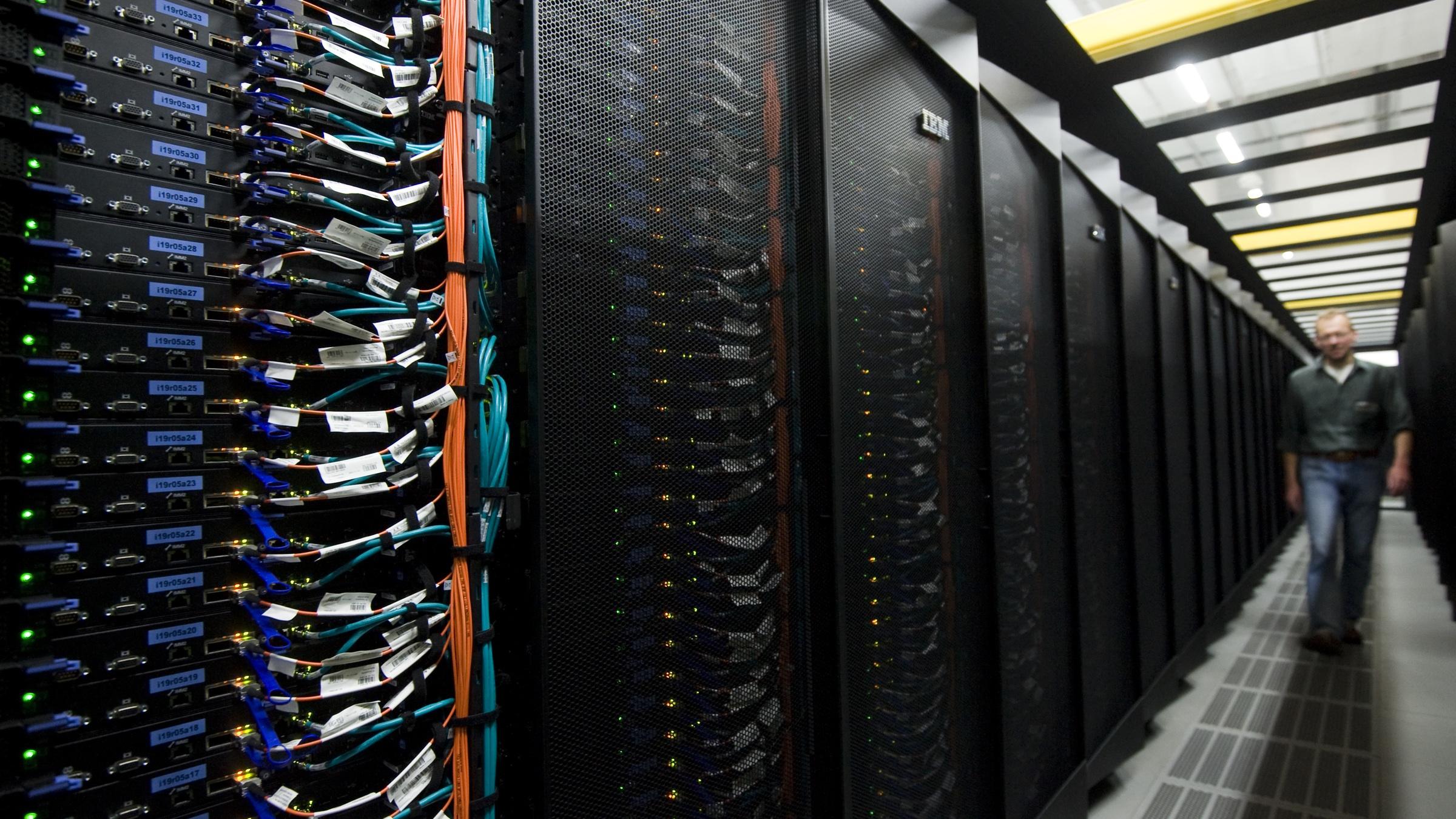 Der Systemadministrator Michael Bopp geht am Freitag (20.07.12) in Garching bei Muenchen im Rechnergebaeude des Hoechstleistungsrechners SuperMUC zwischen Schraenken mit Prozessorkernen. Der schnellste Rechner Europas SuperMUC ist am Freitag in Garching bei Muenchen offiziell in Betrieb genommen worden. SuperMUC ist der viertschnellste Rechner der Welt, teilte die Bayerische Akademie der Wissenschaften am Freitag in Muenchen mit. SuperMUC verfuegt ueber mehr als 155.000 Rechenkerne, die drei Billiarden Rechenoperationen pro Sekunde erbringen. (zu dapd-Text) Foto: Lennart Preiss/dapd