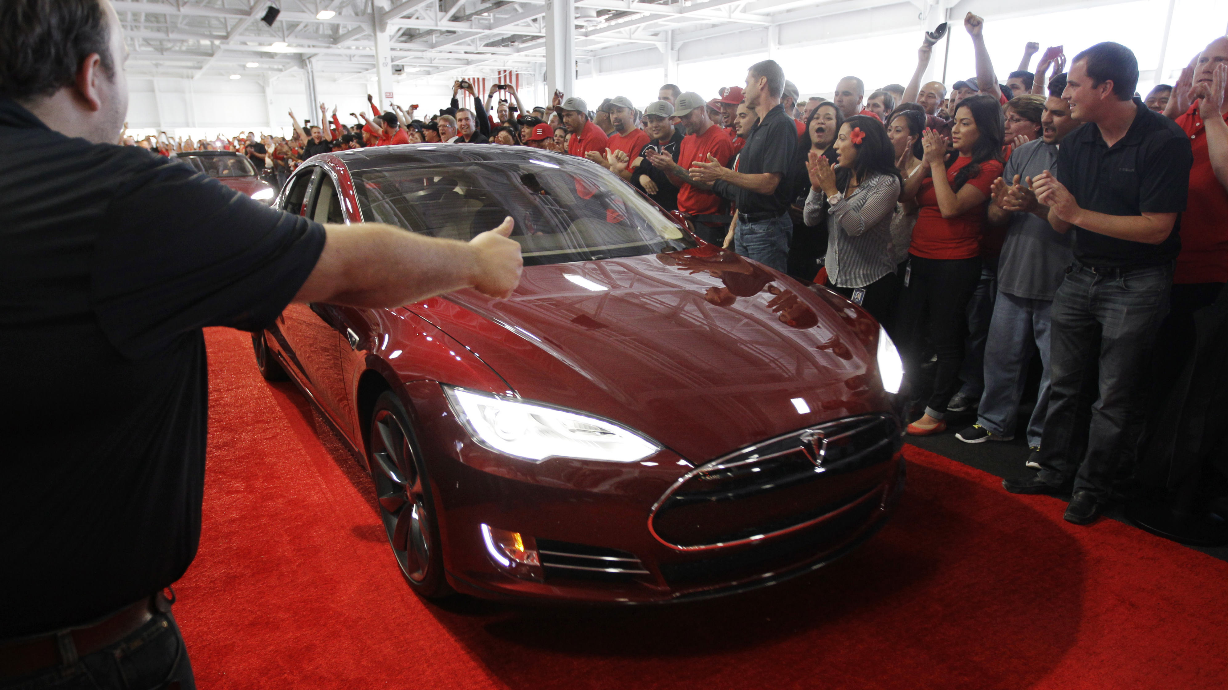 Tesla workers cheer on one the first Tesla Model S cars sold during a rally at the Tesla factory in Fremont, Calif., Friday, June 22, 2012. The first mass-market sedans offered by electric car maker Tesla are now on the road. (AP Photo/Paul Sakuma)