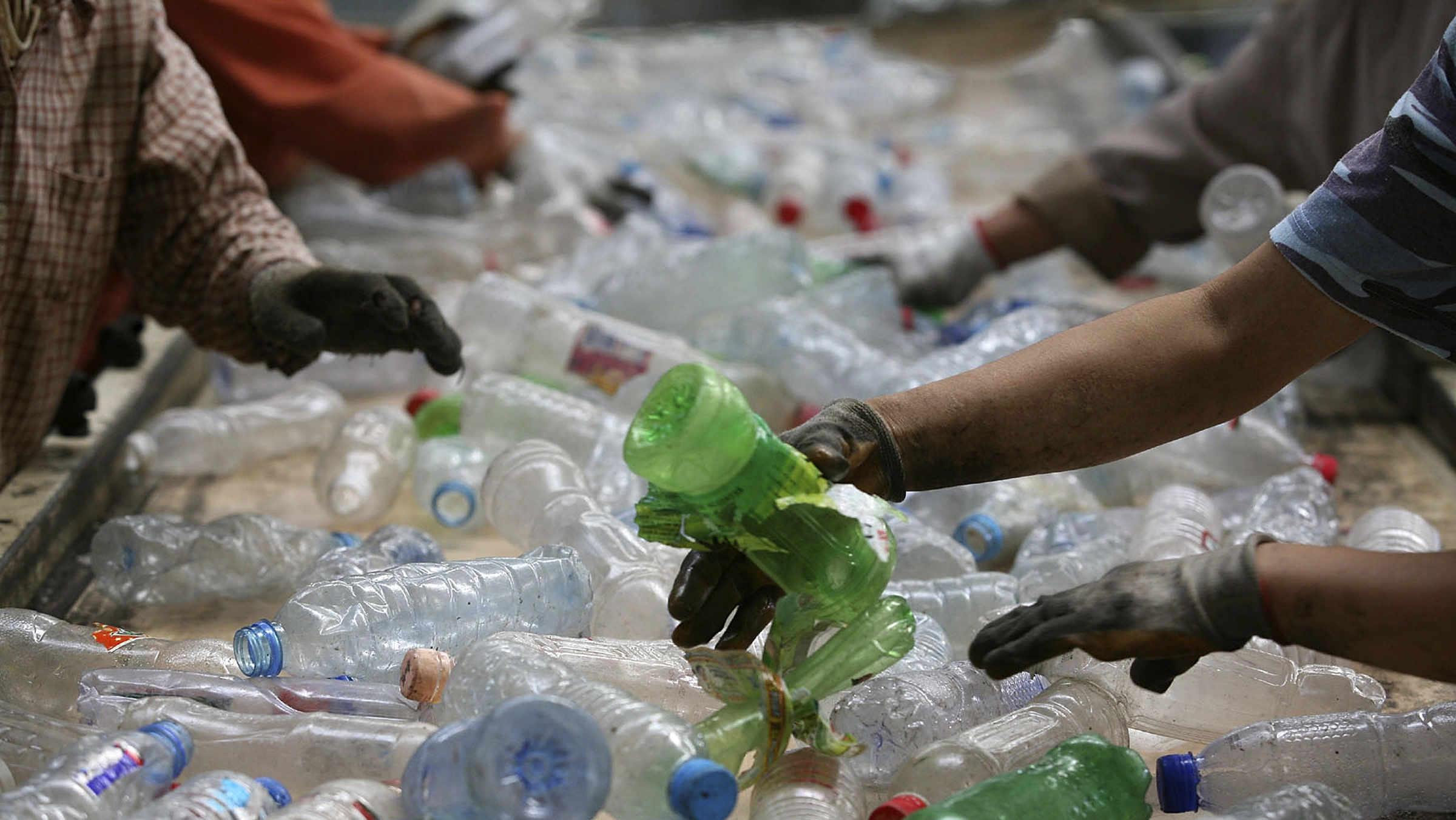 Employees sort plastic bottles at a recycling center in Beijing, China, Sunday, Aug. 30, 2009. (AP Photo