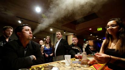 """John Connelly, left, exhales after inhaling marijuana vapor just after midnight Saturday, March 2, 2013, with the help of bar worker Jenae DeCampo, right, in the upstairs lounge area of Stonegate, a pizza-and-rum bar in Tacoma, Wash. Owner Jeff Call charges patrons a small fee to become a member of the private second-floor club, which prohibits smoking marijuana, but does permit """"vaporizing,"""" a method that involves heating the marijuana without burning it. Last fall, Washington and Colorado became the first states to legalize marijuana use for adults over 21."""