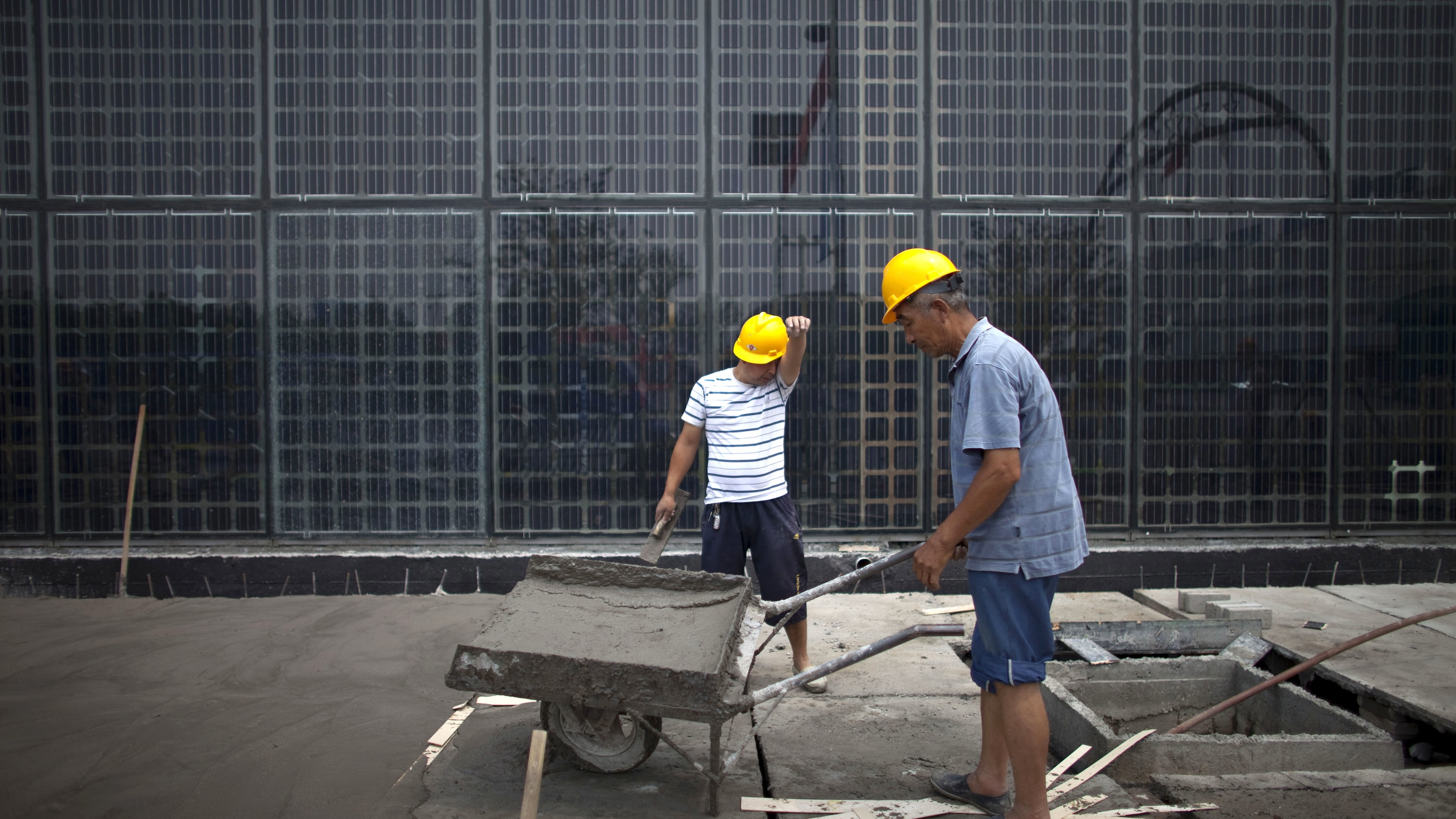 Workers pour and level cement outside a building showing solar walls at a factory of Yingli Green Energy Holding Co. in Baoding, in northern China's Hebei province, Monday, June 20, 2011. (AP Photo/Alexander F. Yuan)