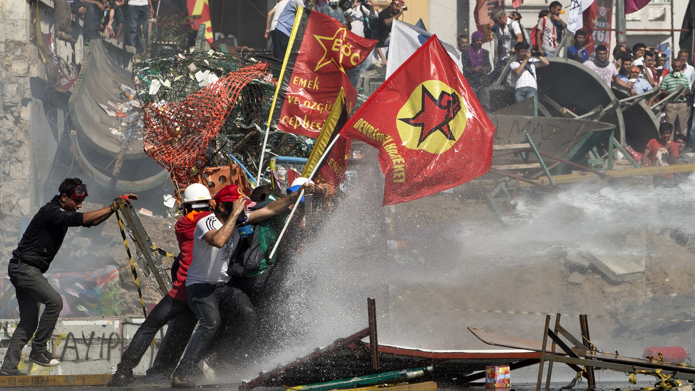 Protesters take cover as a police vehicle fires water canon during clashes at the Taksim Square in Istanbul Tuesday, June 11, 2013. Hundreds of police in riot gear forced their way through barricades in the square early Tuesday, pushing many of the protesters who had occupied the square for more than a week into a nearby park. (AP Photo/Vadim Ghirda)