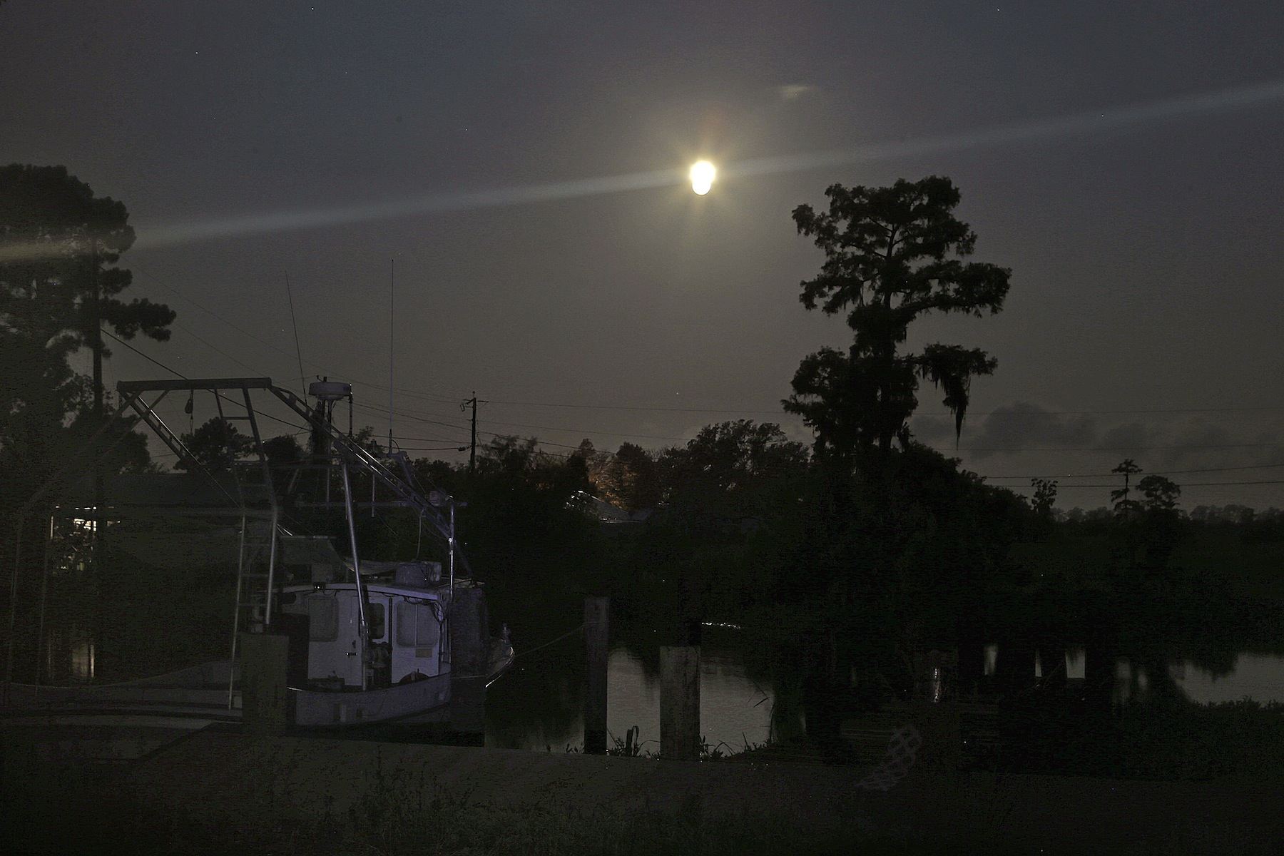 The larger-than-normal full moon referred to as Supermoon is seen setting beyond fishing camps in Akers, La., Sunday, June 23, 2013. (AP Photo/Gerald Herbert)