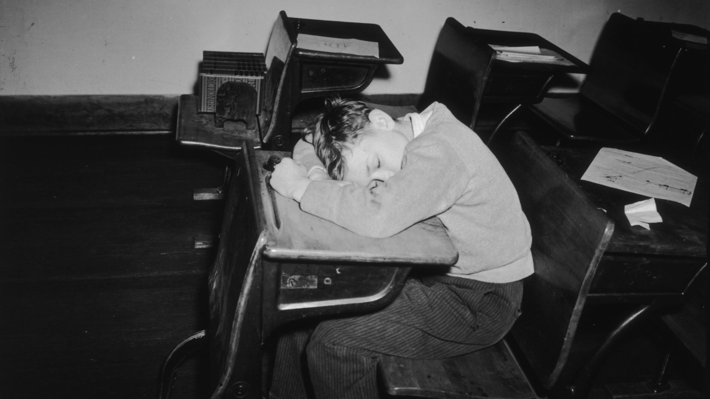 A young boy asleep in class
