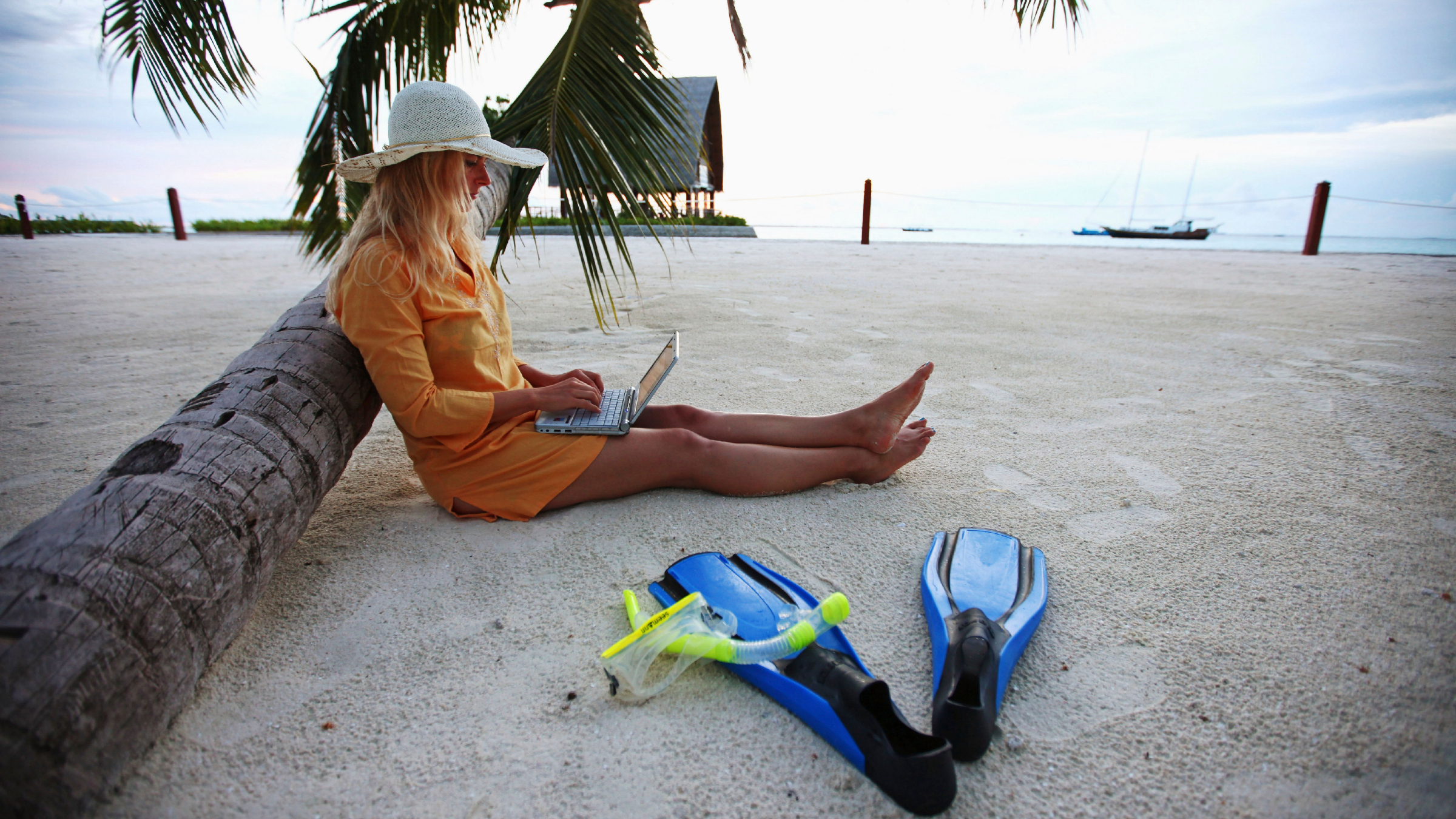 VILLINGILI, ADDU ATOLL , MALDIVES - SEPTEMBER 27: Woman sitting on Villingili beach, working with a notebook and mobile phone, surfing in the internet to run her business The island is owned by the luxurious Shangri-La's Villingili Resort and Spa Hotel on September 27, 2009 in Male, Maldives.The maldive islands consist of around 1100 islands and 400000 inhabitants spread on 220 islands. Till 2008, between 30 years reign of Maumoon Abdul  it was not allowed for tourists to visit local islands without special permission. Now from Villingili Island, tours are possible to visit the local islands of Addu Atoll. (Photo by EyesWideOpen/Getty Images)