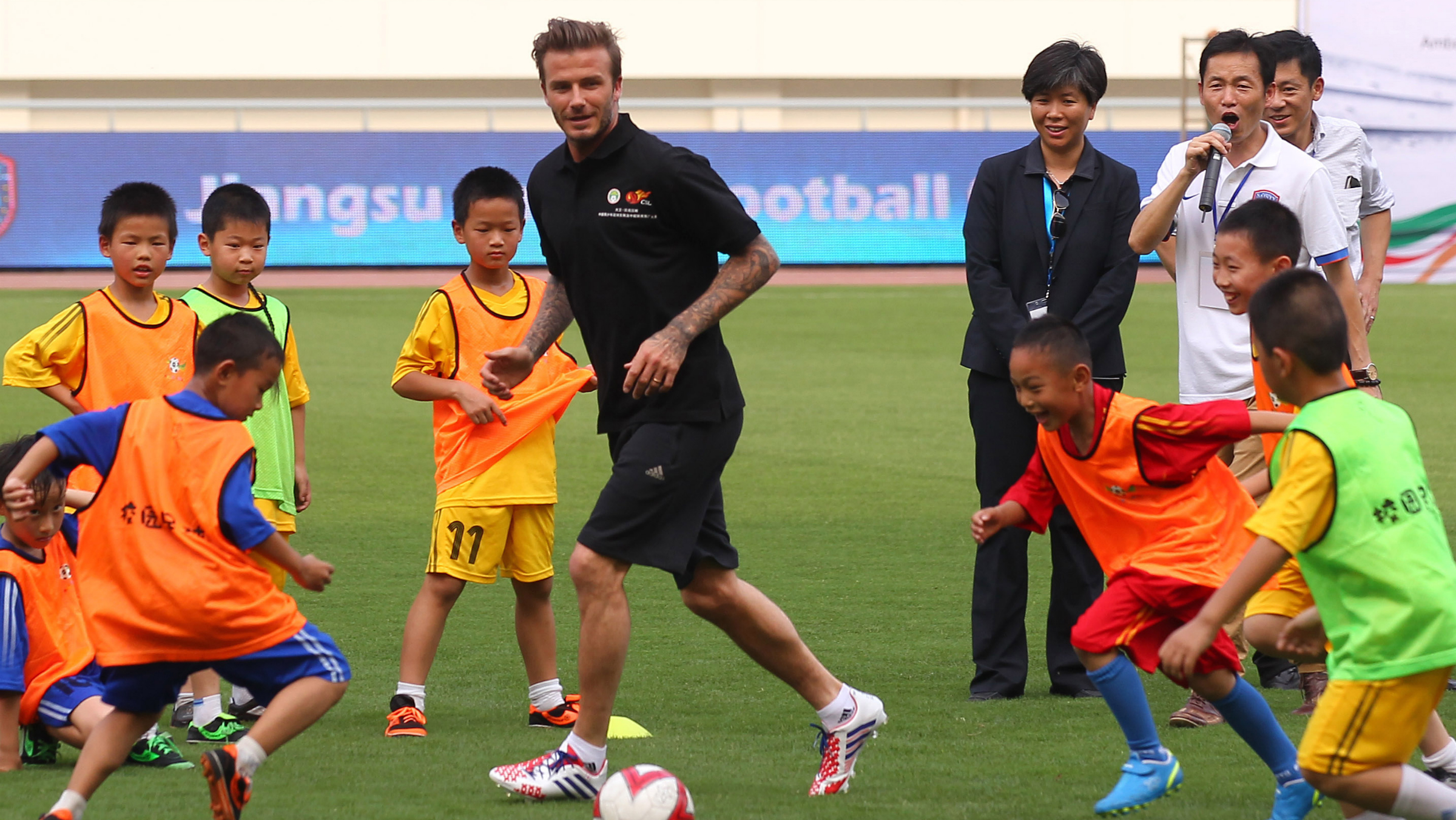 Former England captain David Beckham plays soccer with primary school students at the Olympic Sports Center in Nanjing in east China's Jiangsu province on Tuesday, June 18, 2013. Beckham is on a 7-day visit in China as ambassador to Chinese Super League.(Photo By Yang Bo/Color China Photo/AP Images