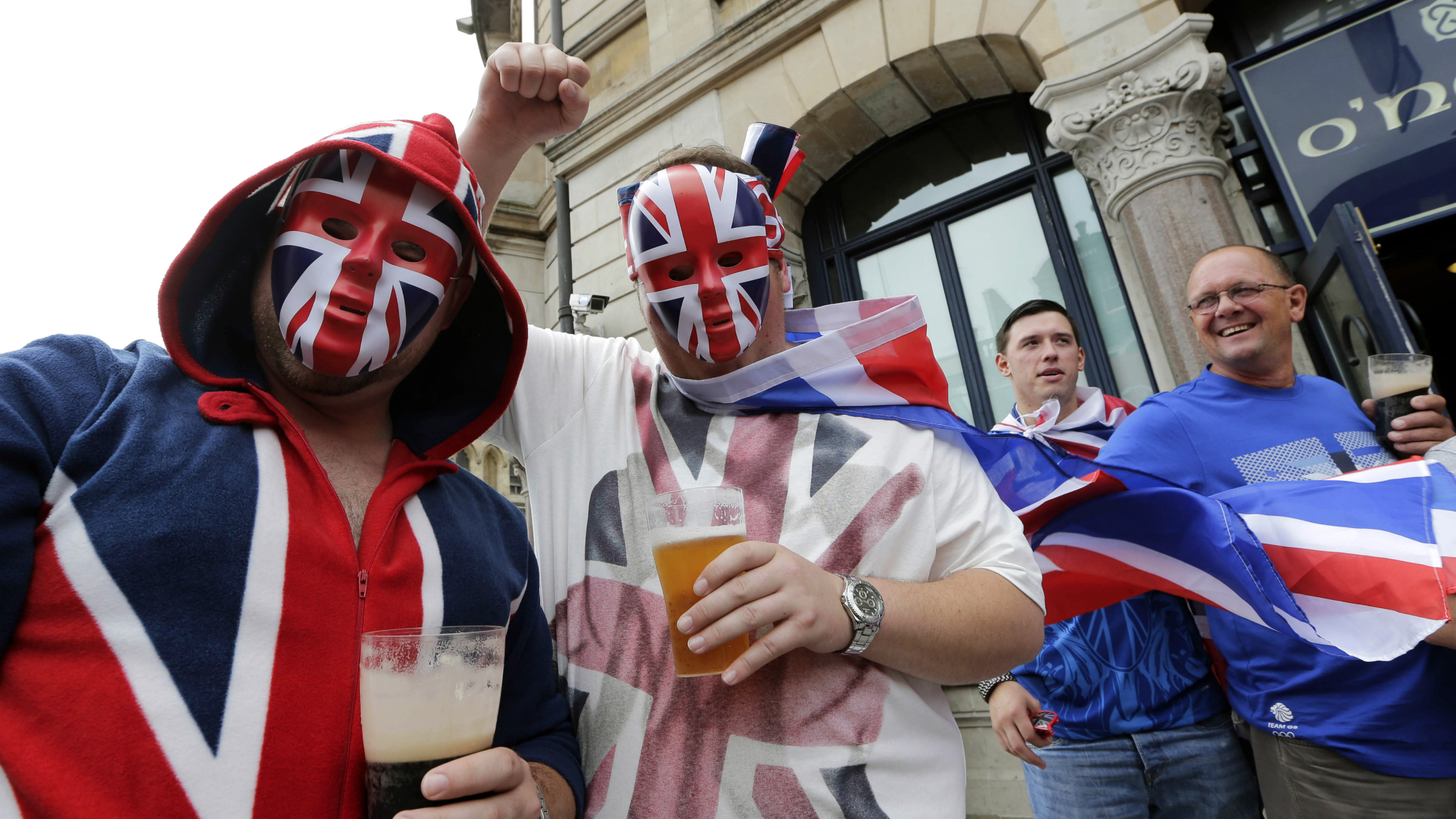 British supporters drink beer outside a pub prior to the start of the men's group A soccer match between Britain and Uruguay, at the Millennium Stadium in Cardiff, Wales, at the 2012 London Summer Olympics, Wednesday, Aug. 1, 2012. (AP Photo/Luca Bruno