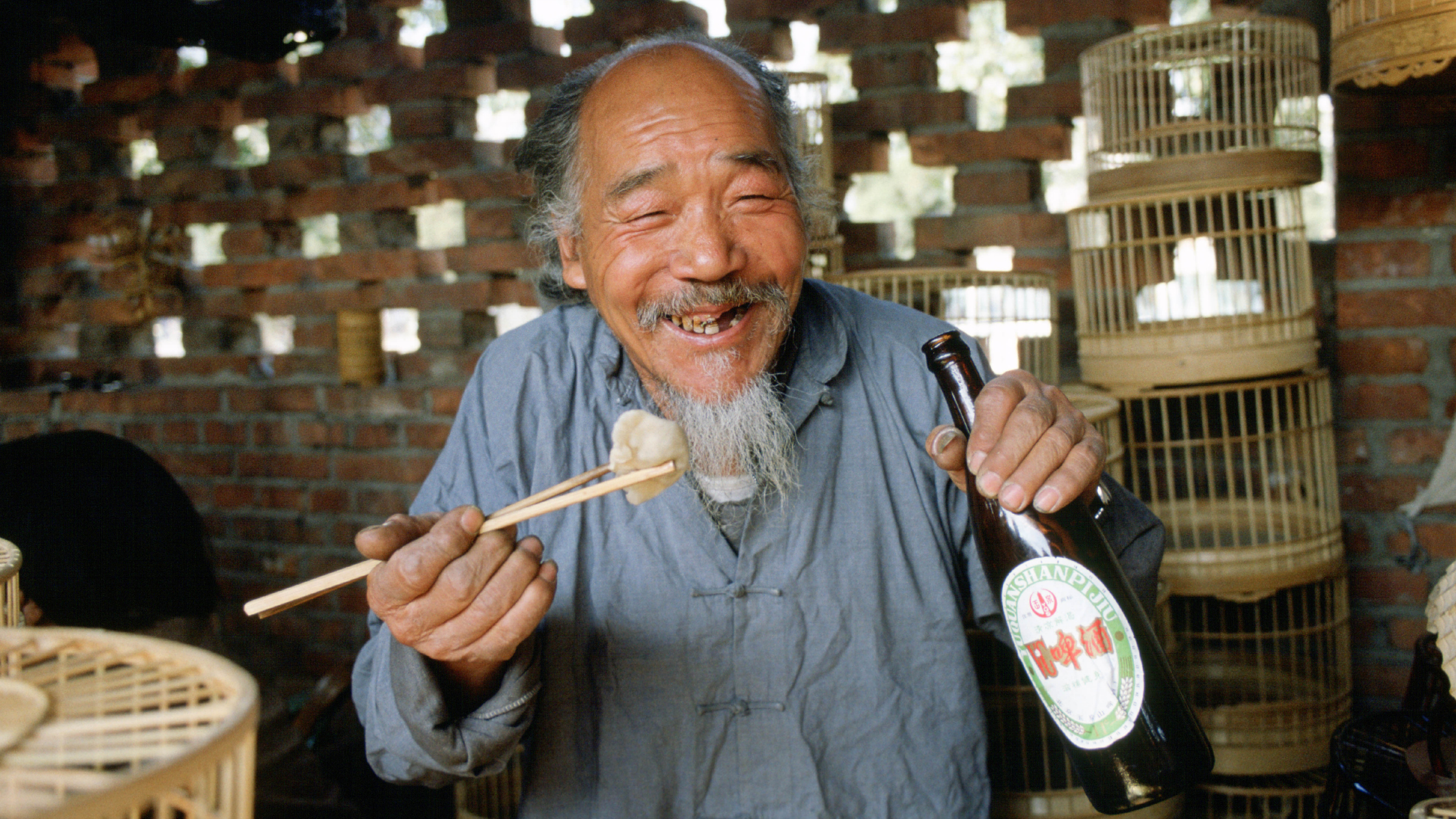 Man eating with chopsticks and drinking beer.