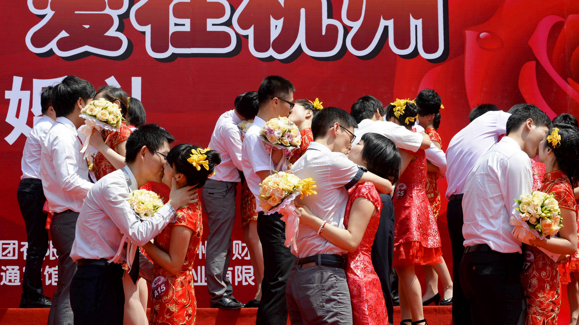 """Couples kiss as they participate in a mass wedding ceremony in Hangzhou, Zhejiang province May 19, 2013. According to local media, a total of 80 couples attended the ceremony on Sunday. The characters collectively read: """"Love in Hangzhou"""". REUTERS/Stringer"""