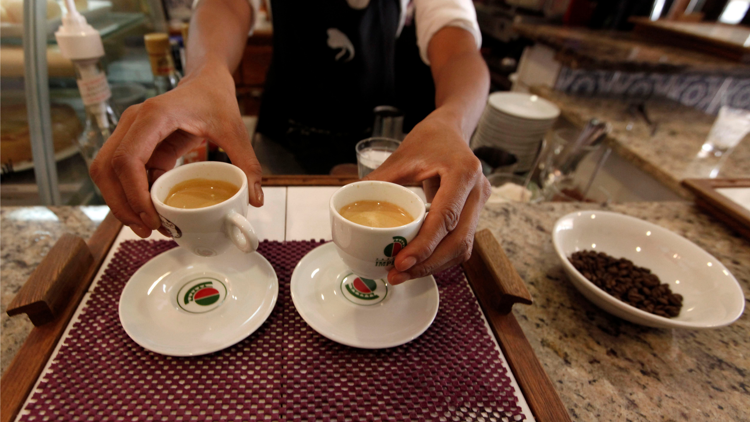 A waitress serves coffee to customers at a coffee bar in Sao Paulo.