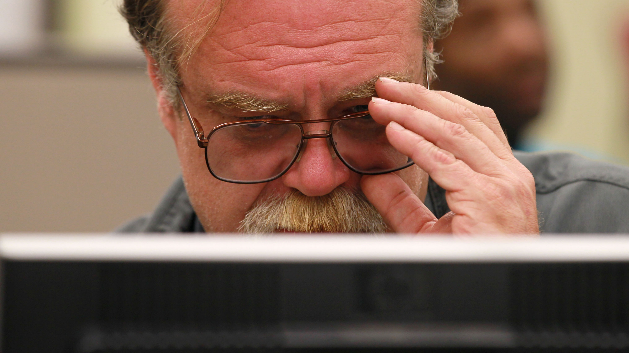 Man holds glasses while sitting at computer