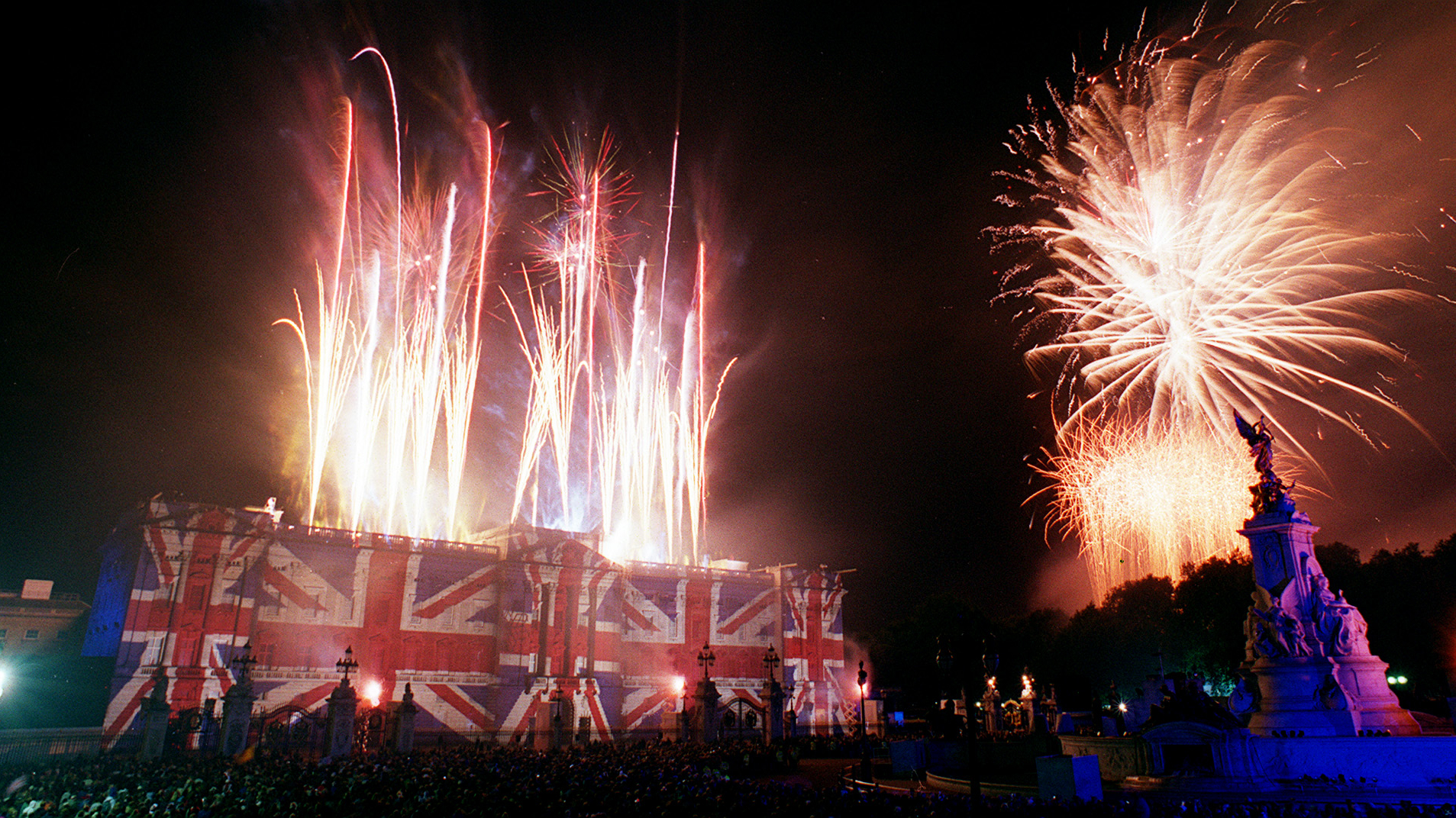 Fireworks light up the sky over Buckingham Palace, lit in colours of the Union flag after the Party At the Palace as part of the Golden Jubilee celebrations in London Monday, June 3, 2002. Britain's Queen Elizabeth has been the British monarch for 50 years, since the death of her father George VI in 1952. (AP Photo/Steve Holland
