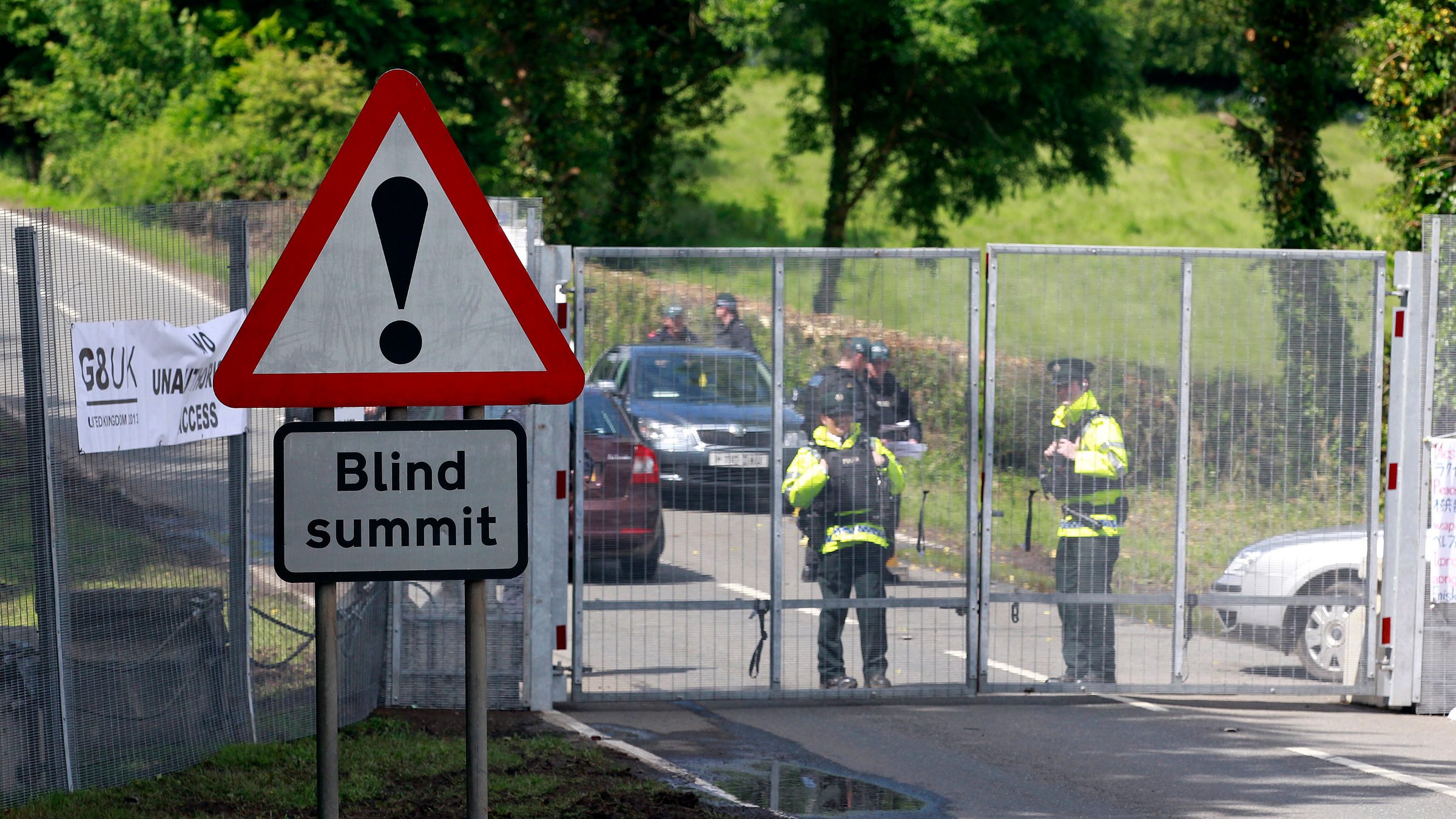 Police officers guard the security fence surrounding the G8 Summit at Lough Erne in Enniskillen, Northern Ireland June 17, 2013.