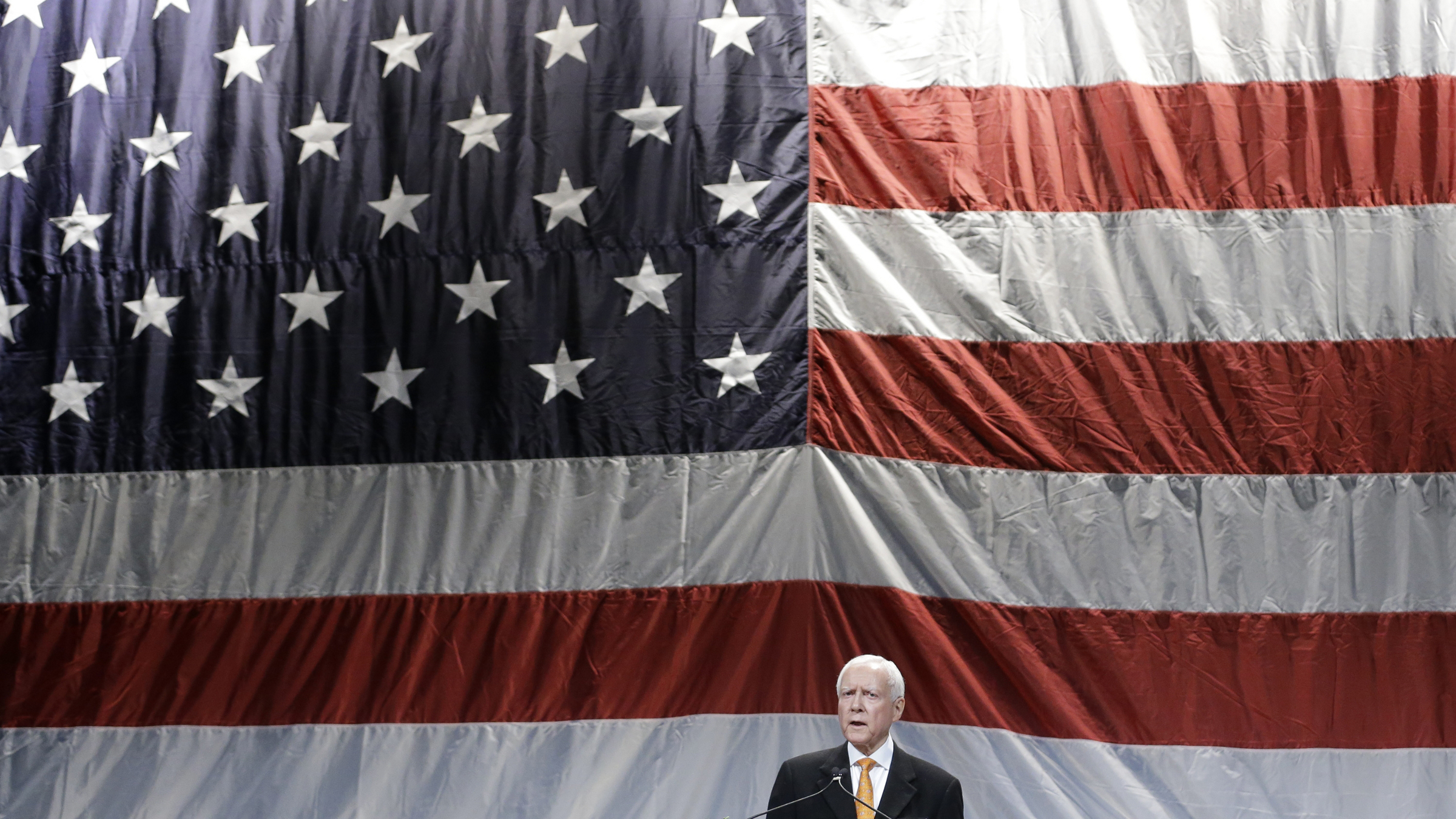 This May 18, 2013, file photo, Republican Sen. Orrin Hatch addresses the Utah Republican Party's annual organizing convention, in Sandy, Utah. Hatch says he'll vote in favor of the latest immigration reform package, retreating from his demand that the Senate bill require immigrants here illegally to pay back taxes.