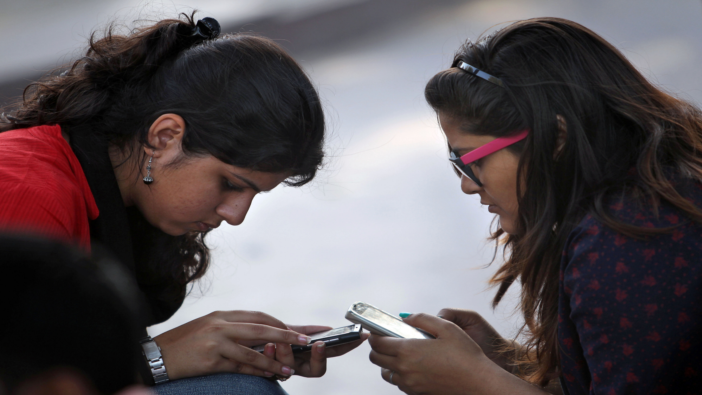 Indian girls engage with their mobile phones in New Delhi, India, Thursday, Feb. 28, 2013. Indian Finance minister Palaniappan Chidambaram unveiled a national budget with a promise to put Asia's third largest economy back on a path of high growth and to check runaway inflation and the fiscal deficit. He hiked taxes on imported luxury cars, high-end motorcycles and yachts, all of which have become symbols of affluence among India's upper classes and said mobile phones and SUVs would cost more, as would dining at expensive restaurants. (AP Photo/Tsering Topgyal)