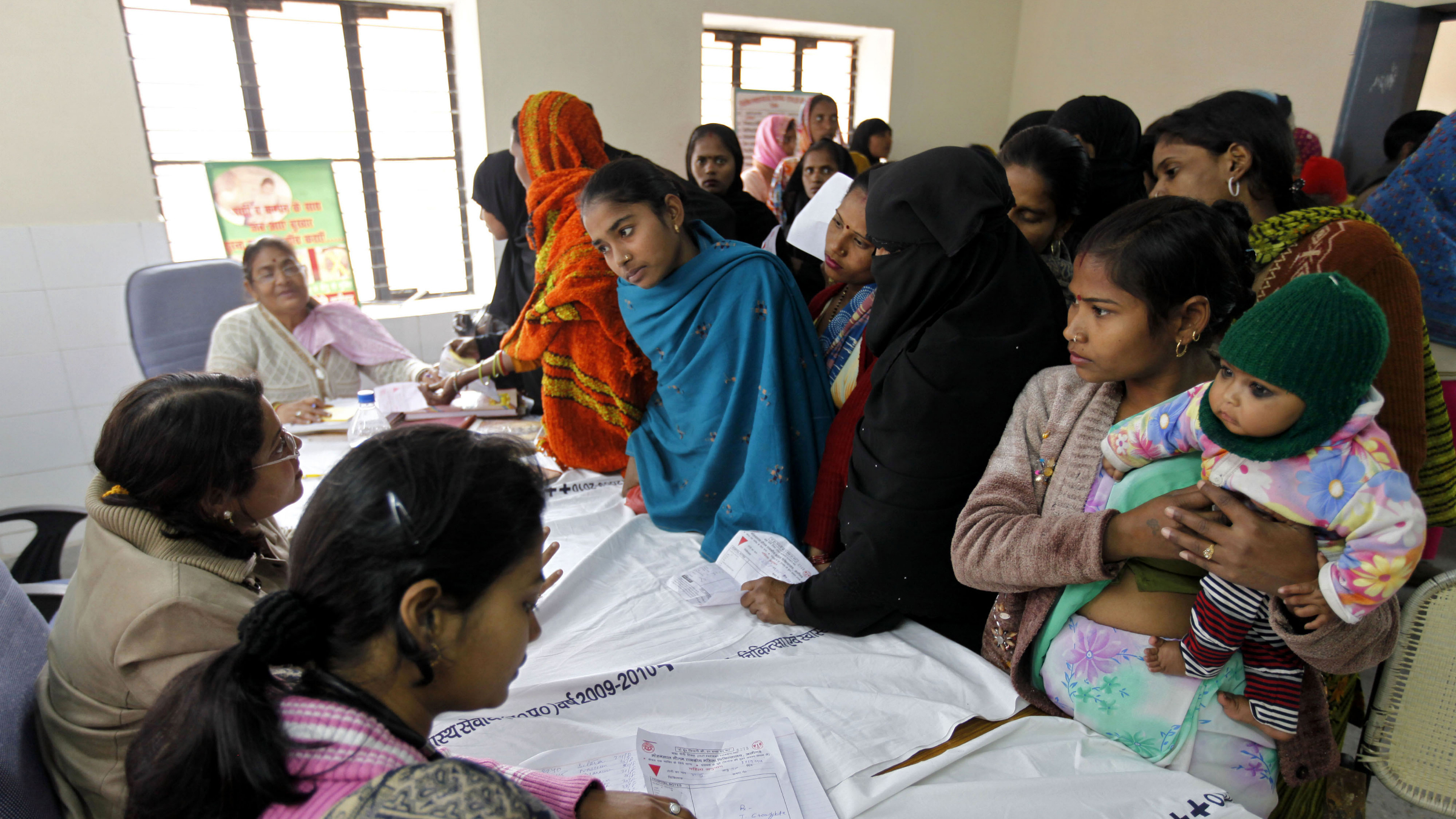 In this Feb. 4, 2011 photo, patients get registered for a free sterilization procedure at the Mohan Lal Gautam District Women's Hospital in Aligarh, India. Every day dozens of women line up at this hospital for a free sterilization procedure that will spare them the risk and cost of having another child. The hospital's three staff doctors race through seeing some 500 patients a day needing help with childbirth, pelvic inflammatory diseases, abortions and other treatments at subsidized costs. Each year, the cost of health care pushes some 39 million people into poverty, with patients shouldering up to 80 percent of India's medical costs. (AP Photo/Mustafa Quraishi