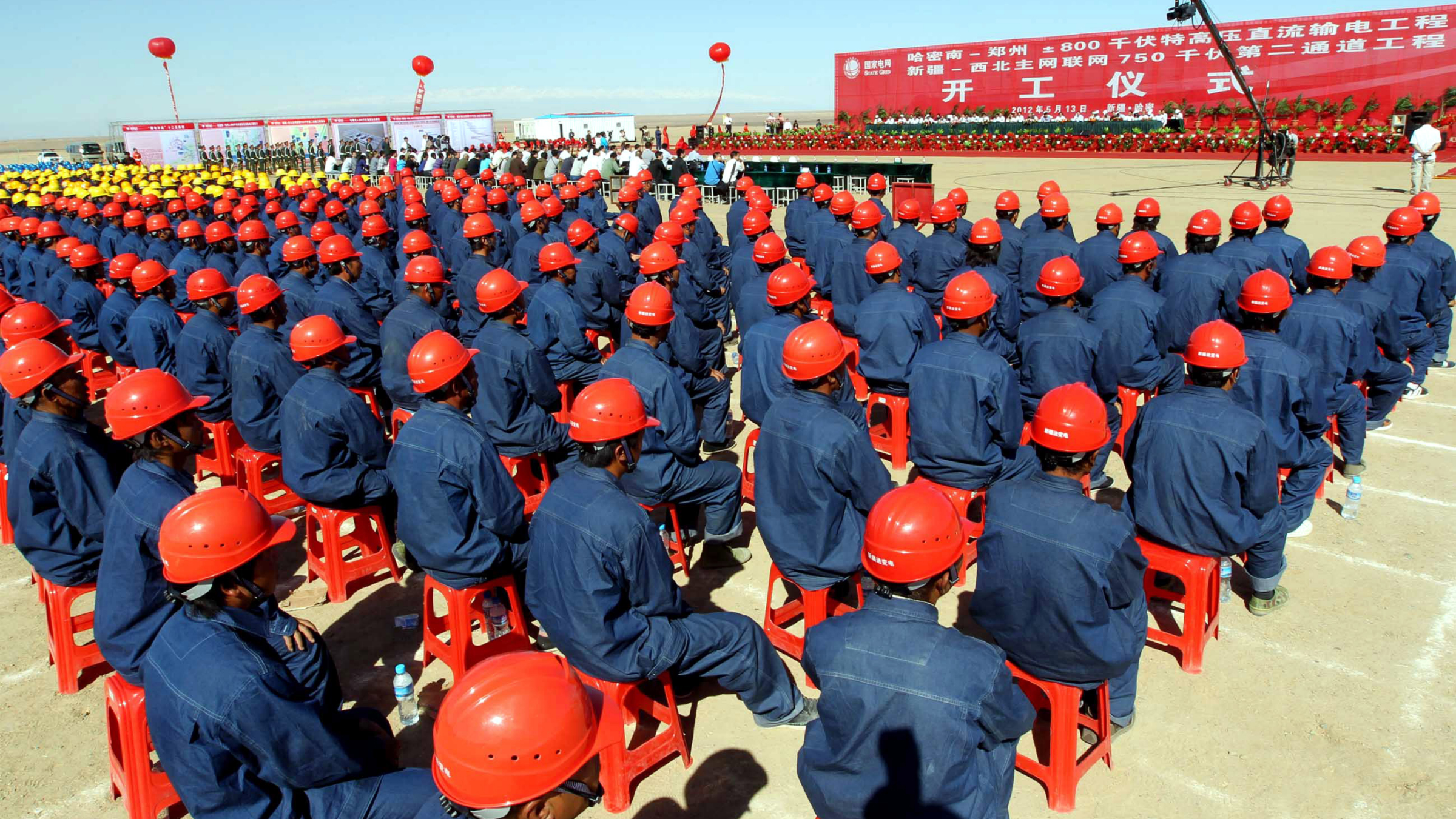 Chinese workers from the State Grid Corporation of China attend the groundbreaking ceremony for a converter station of the 800 kilovolt (kv) ultra-high voltage power line project in Hami prefecture, northwest Chinas Xinjiang province, 13 May 2012. China took a major step towards upgrading its energy infrastructure by announcing the construction of the worlds largest transmission line, a massive 800 kilovolt (kv) ultra-high voltage power line that is capable of transmitting a whopping 37 billion kWh per year. Built by the State Grid Corporation of China, the high-capacity power line will stretch 1,373 miles from Hami prefecture in northwest Chinas Xinjiang region through Gansu, Shaanxi, Ningxia and Shanxi before finishing in Zhengzhou, the capital of central Chinese province of Henan. The power line costs 23.39 billion yuan (US$3.7 bn). Once it is completed in 2014, it will have a world record capacity of eight million kW.(Imaginechina via AP Images
