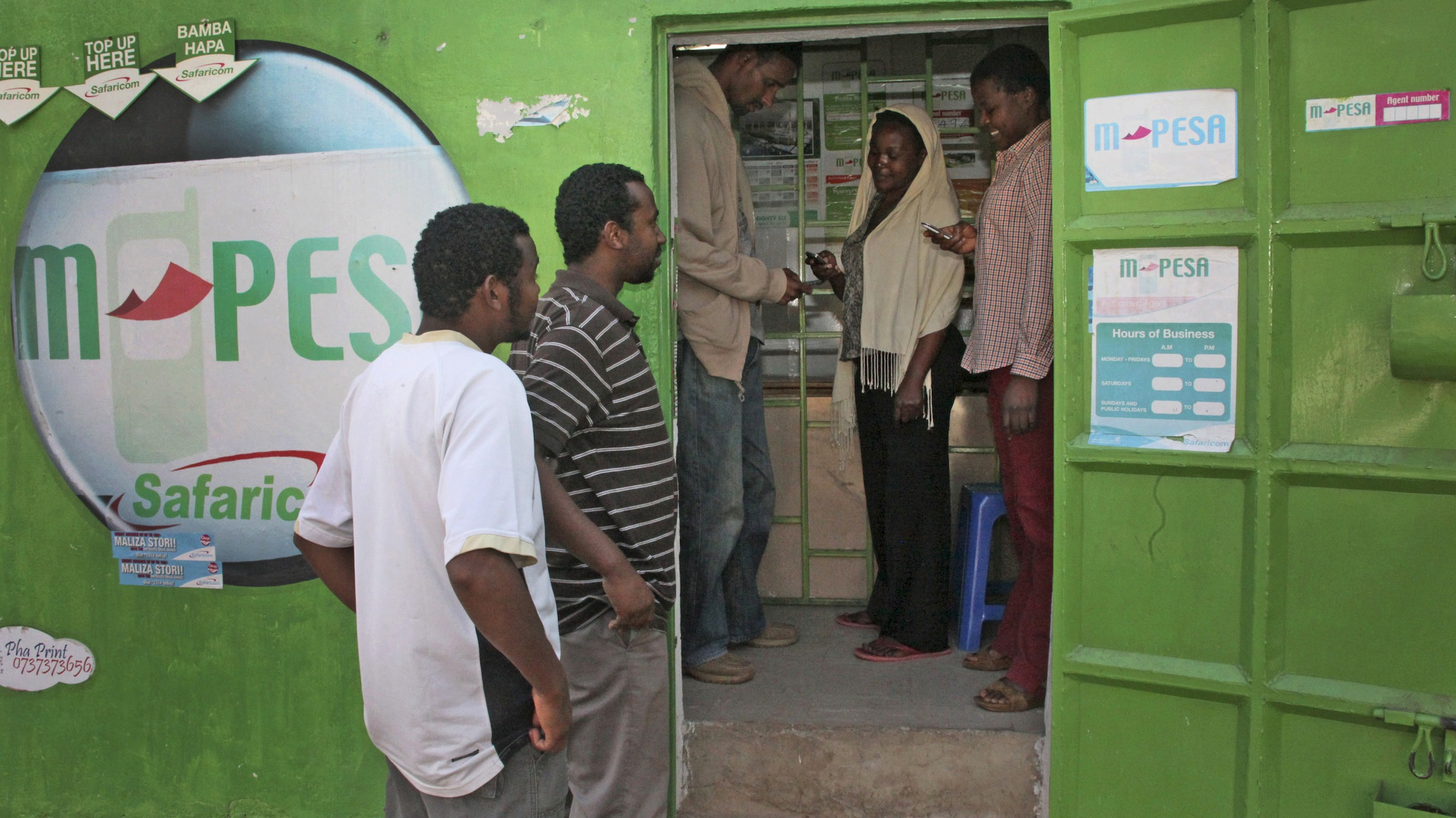 In this photo of Wednesday Aug. 24, 2011 customers make money transfers at an M-Pesa counter in Nairobi, Kenya, as others wait outside. A mobile phone banking service called M-Pesa allows people without a bank account to transfer money between phones instantly anywhere in the country. More than 50 countries now have such services, including Afghanistan. The fundraising effort Kenyans for Kenya has raised more than $7 million for drought victims. Bob Collymore, the head of telelphone company Safaricom, said more than 86 percent of early donations to the campaign came through M-Pesa.(AP Photo/Sayyid Abdul Azim)