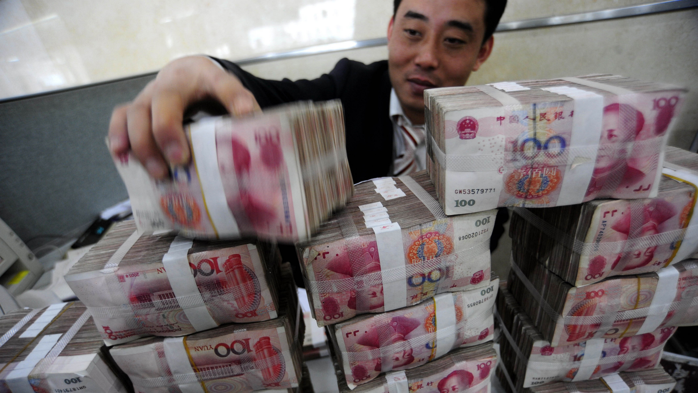 In this file photo taken on Nov. 17, 2009, a bank clerk stacks up renminbi banknotes at a bank in Hefei in central China's Anhui province. China has ordered its banks to hold back more money as reserves in a new move to curb lending and cool inflation. The order Friday Nov. 19, 2010, was China's second reserve increase in two weeks and came as Beijing tries to restore normal financial conditions and curb inflation after its recovery from the global crisis. (AP Photo