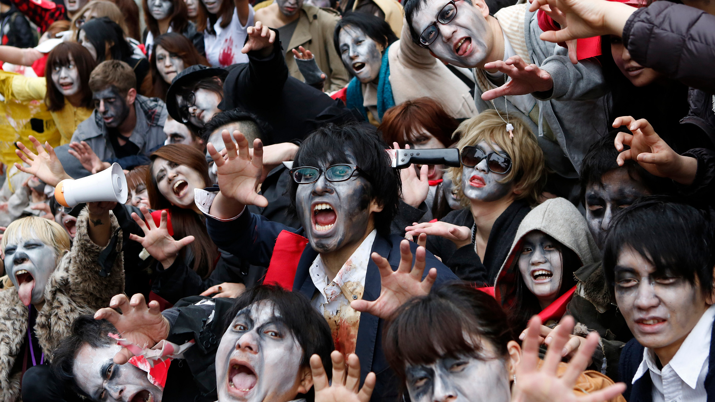 People, dressed as zombies, pose for photos after the Roppongi Zombie Walk in Tokyo March 31, 2013. About 50 people dressed up as zombies early evening on Sunday, catching the attention of pedestrians on the streets of Tokyo's downtown Roppongi district.