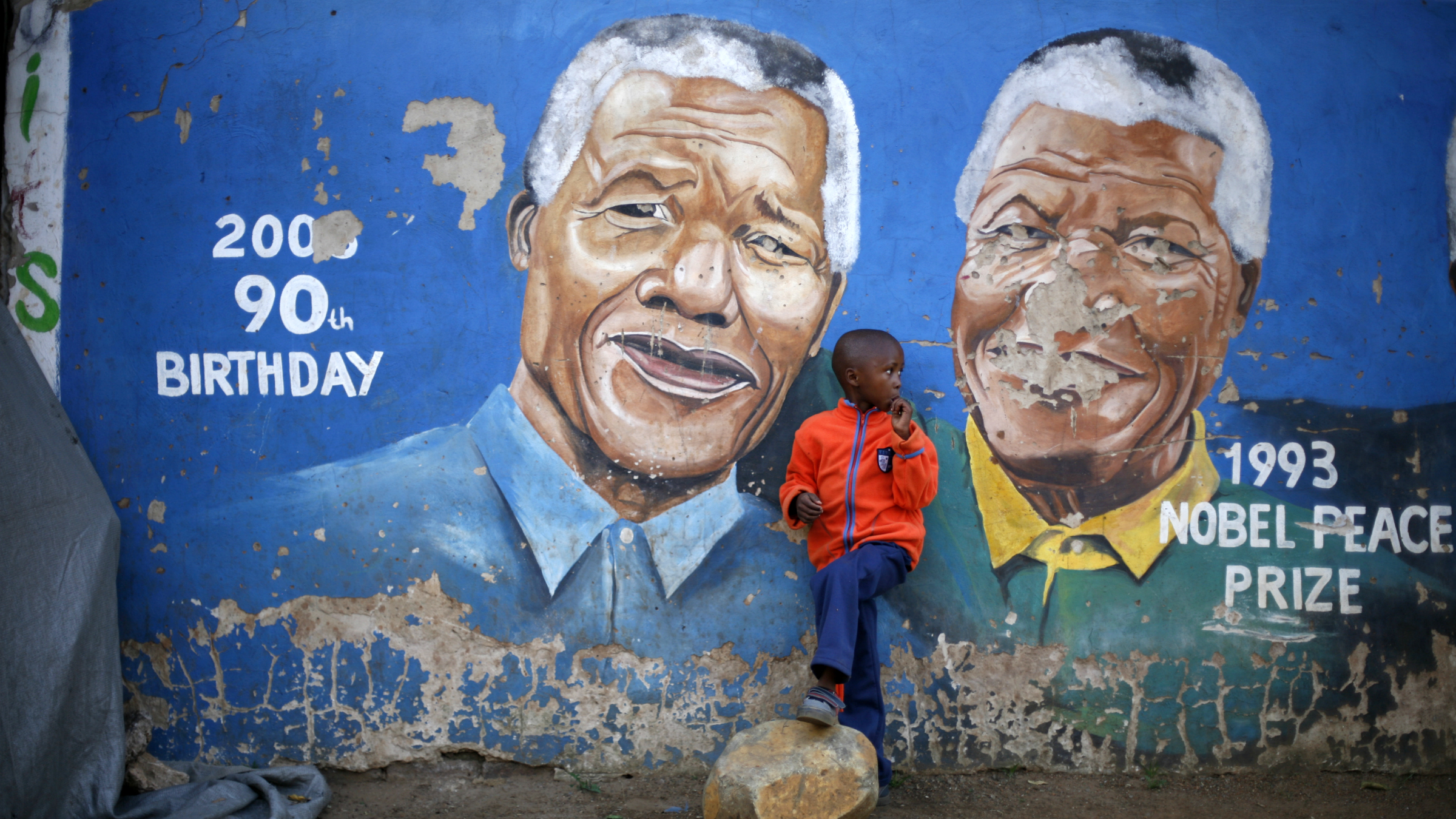 A young boy stands by a mural of Nelson Mandela in the Soweto township in Johannesburg, South Africa.