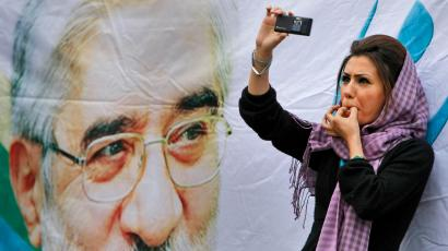 In this June 9, 2009 file picture, a supporter of main challenger and reformist candidate Mir Hossein Mousavi, standing next to a poster of him, whistles as she films the event with her mobile phone, amidst a festive atmosphere at an election rally at the Heidarnia stadium in Tehran, Iran. An opposition activist spreads word of an upcoming protest in the streets of Tehran. Another posts pictures of clashes between demonstrators and police. As Iran's government cracks down on traditional media after the country's disputed presidential election, tech-savvy Iranians have turned to the microblogging site Twitter.