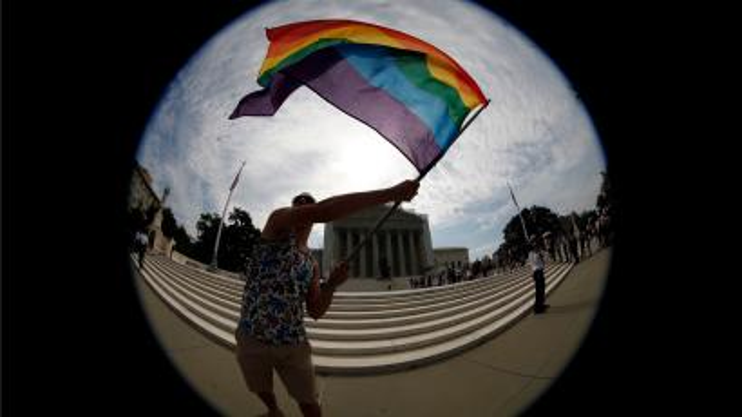Man waving rainbow flag.