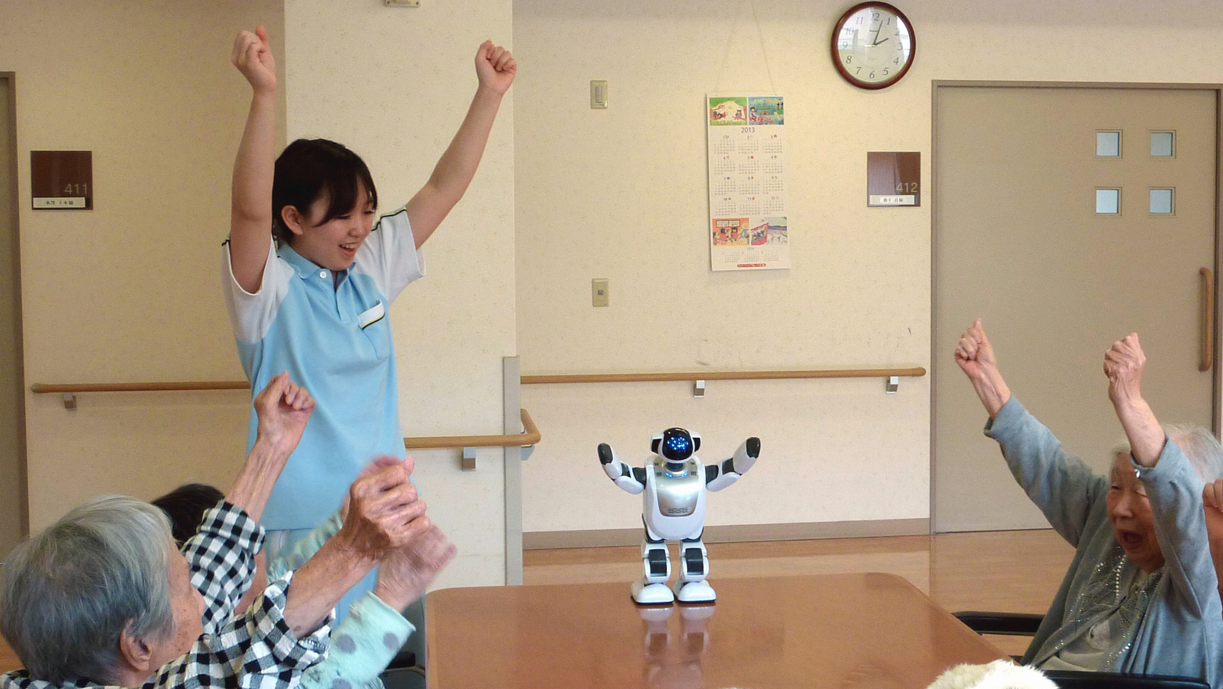 YOKOHAMA, Japan - Residents at the Fuyouen senior citizen's home in Yokohama, Kanagawa Prefecture, interact with Palro, a humanoid robot, on May 10, 2013. Seen in front are two baby seal-like Paro therapy robots. (Kyodo via AP Images