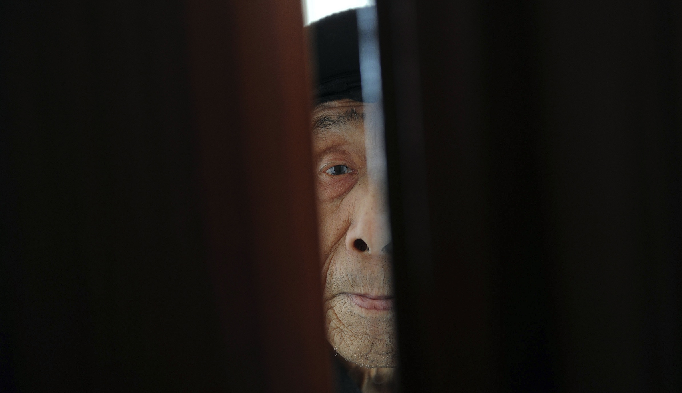 An elderly man looks out from a door at a nursing home in Hefei, Anhui province March 20, 2012. China's efforts to overhaul the world's biggest healthcare system and the increased medical care demanded by a more prosperous and aging nation will push costs higher, according to Health Minister Chen Zhu. Picture taken March 20, 2012. REUTERS/Stringer (CHINA - Tags: POLITICS SOCIETY HEALTH) - RTR2ZNCK