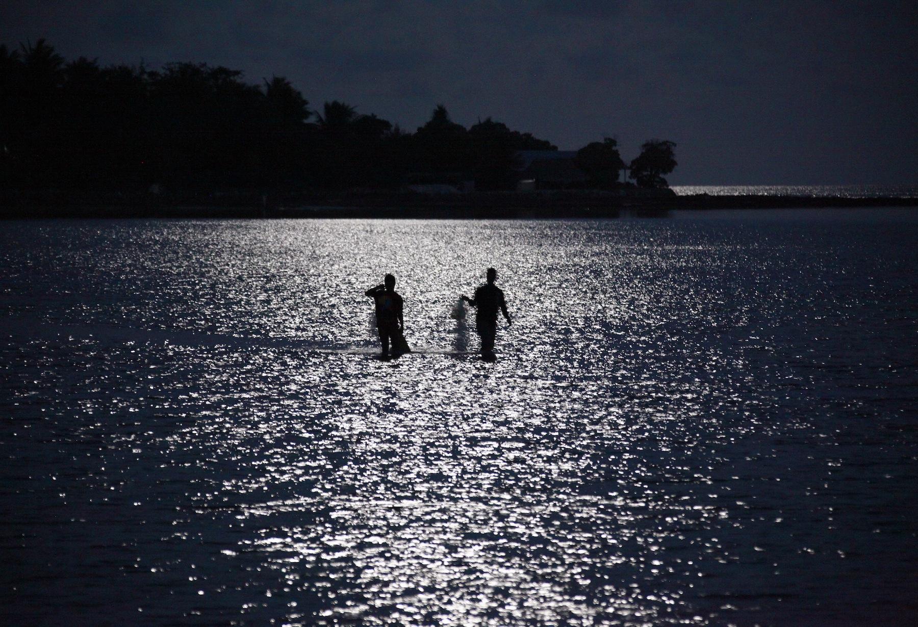 Fishermen are illuminated by the full moon as they prepare to cast their nets near the village of Teaorereke on South Tarawa in the central Pacific island nation of Kiribati May 25, 2013. REUTERS/David Gray (KIRIBATI - Tags: ENVIRONMENT SOCIETY POLITICS) - RTX10NEU