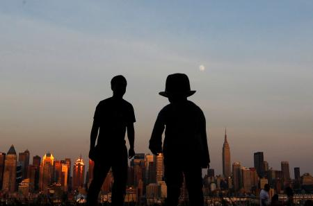 """A father and his son watch the moon rise over the skyline of New York from a lookout in Weekhawken, New Jersey, June 21, 2013. On Saturday a perigee moon will coincide with a full moon creating a """"super moon"""" when it will pass by the earth at its closest point in 2013. REUTERS/Gary Hershorn (UNITED STATES - Tags: CITYSCAPE SCIENCE TECHNOLOGY ENVIRONMENT) - RTX10WOF"""