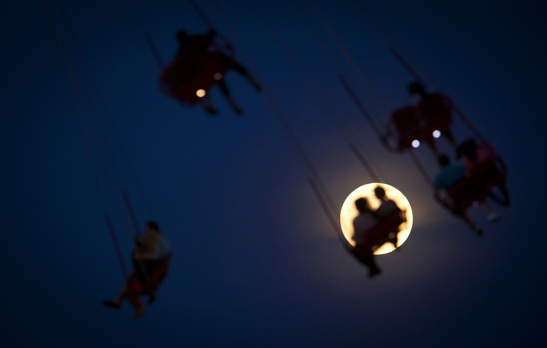 """People ride the Luna Park Swing Ride as the Super Moon rises on Coney Island, June 22, 2013. The largest full moon of the year called the """"super moon"""" will light up the night sky this weekend. REUTERS/Carlo Allegri (UNITED STATES - Tags: ENVIRONMENT SOCIETY TPX IMAGES OF THE DAY) - RTX10XOP"""