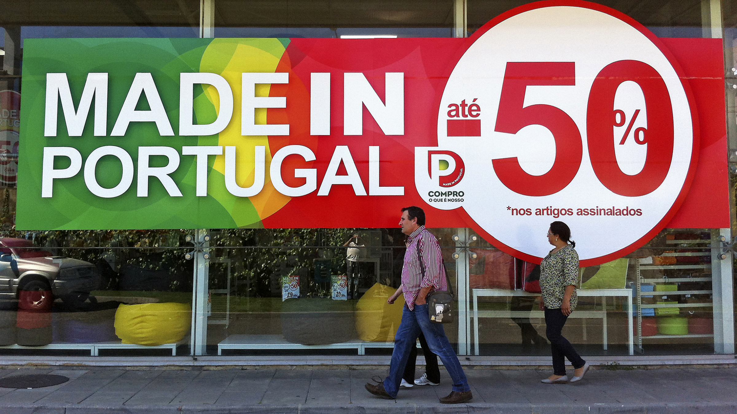 """People walk past a shop window with an announcement of discounts going up to 50 percent on goods made in Portugal, in Sintra April 23, 2013. Portugal's government plans to lower company tax rates """"significantly"""" as part of a wider plan of incentives to drag the economy out of its worst recession since the 1970s, Economy Minister Alvaro Santos Pereira said on Tuesday. REUTERS/Jose Manuel Ribeiro (PORTUGAL - Tags: POLITICS BUSINESS)"""