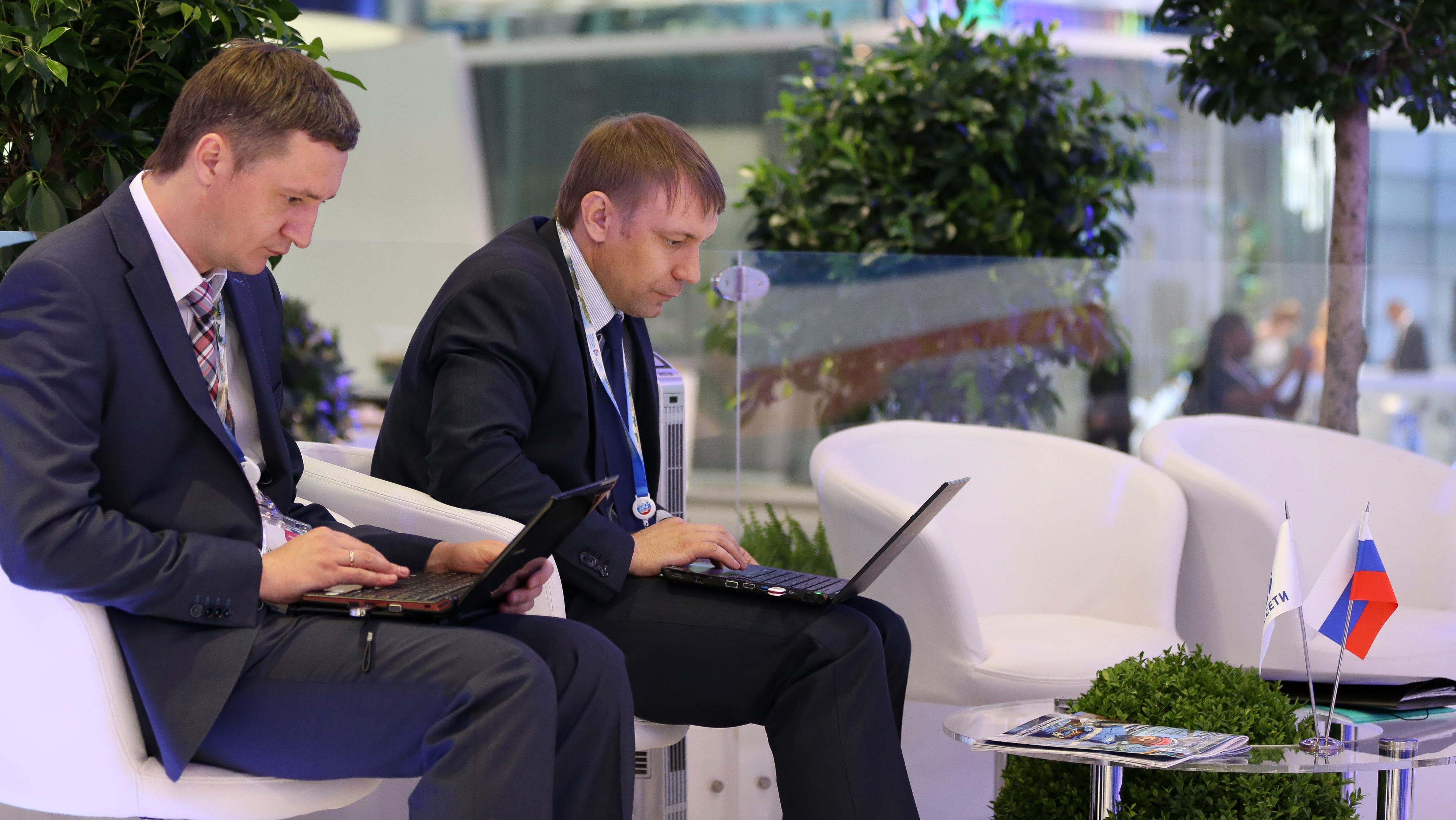 Attendees work on laptop computers near a Russian national flag in a conference hall on day two of the St. Petersburg International Economic Forum 2013 (SPIEF) in St. Petersburg, Russia, on Friday, June 21, 2013. President Vladimir Putin is battling investor skepticism to woo foreign executives descending on his hometown today as Russia's economy faces a risk of recession and a crackdown on critics scares off intellectuals. Photographer: Andrey Rudakov/Bloomberg