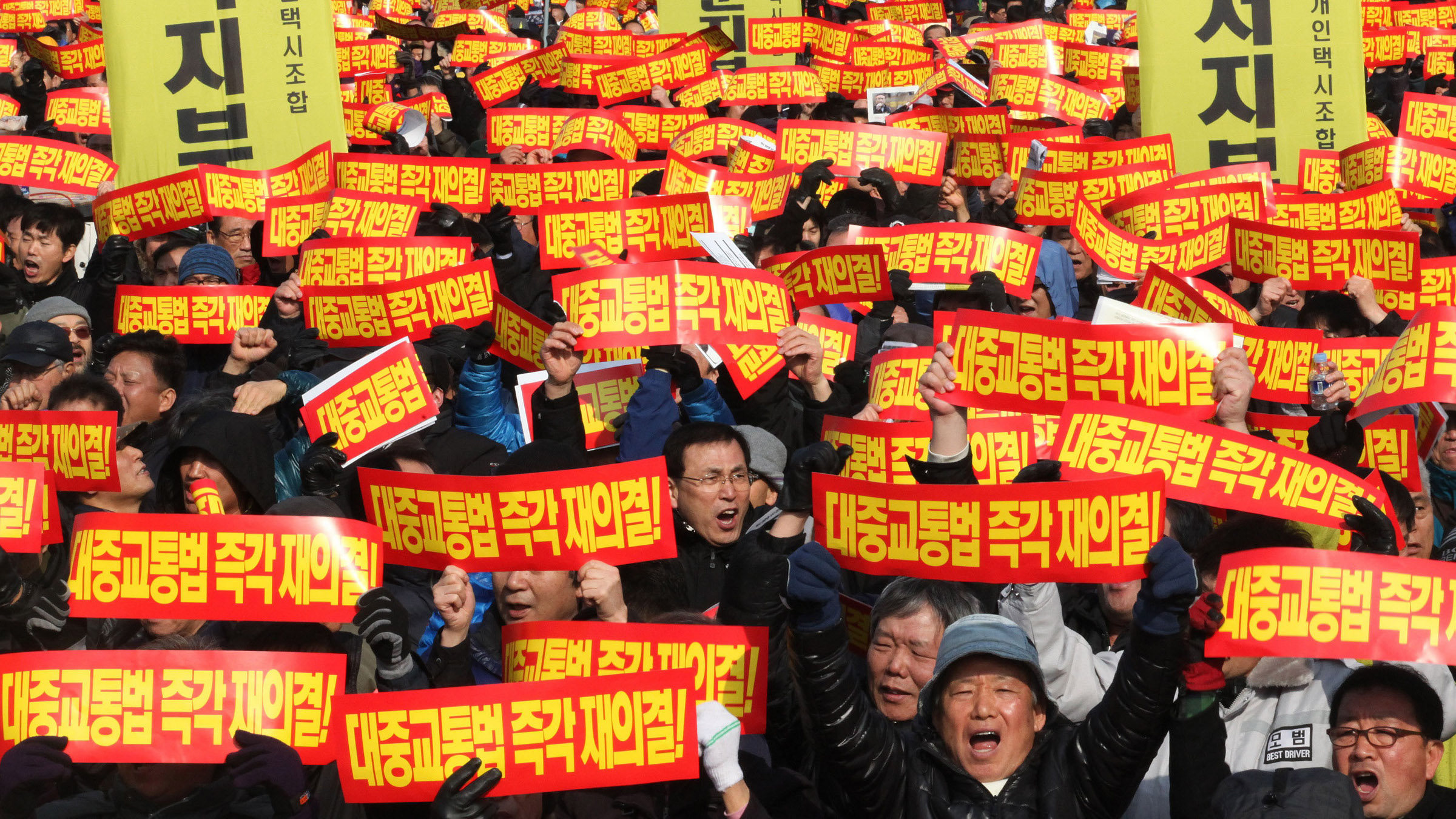 "About 20,000 taxi drivers shout slogans during a rally against government policy near the National Assembly in Seoul, South Korea, Wednesday, Feb. 20, 2013. They launched one-day strike on Wednesday to demand the National Assembly to revive a vetoed taxi bill that would have allowed taxies to be recognized as public transportation near the National Assembly. The letters read "" Taxies to be recognized as public transportation""."